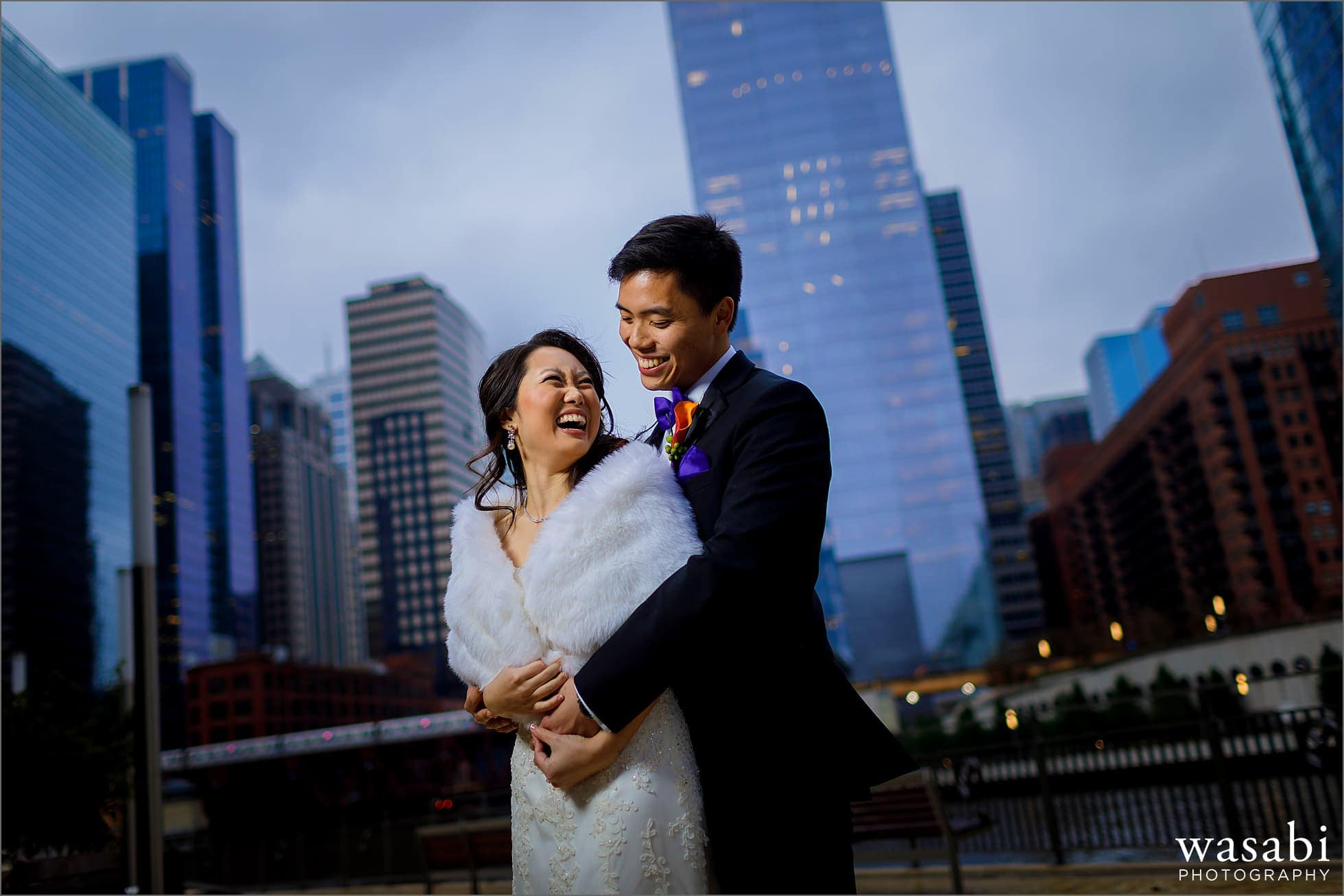 lit portrait of bride and groom with Chicago skyline and river in the background