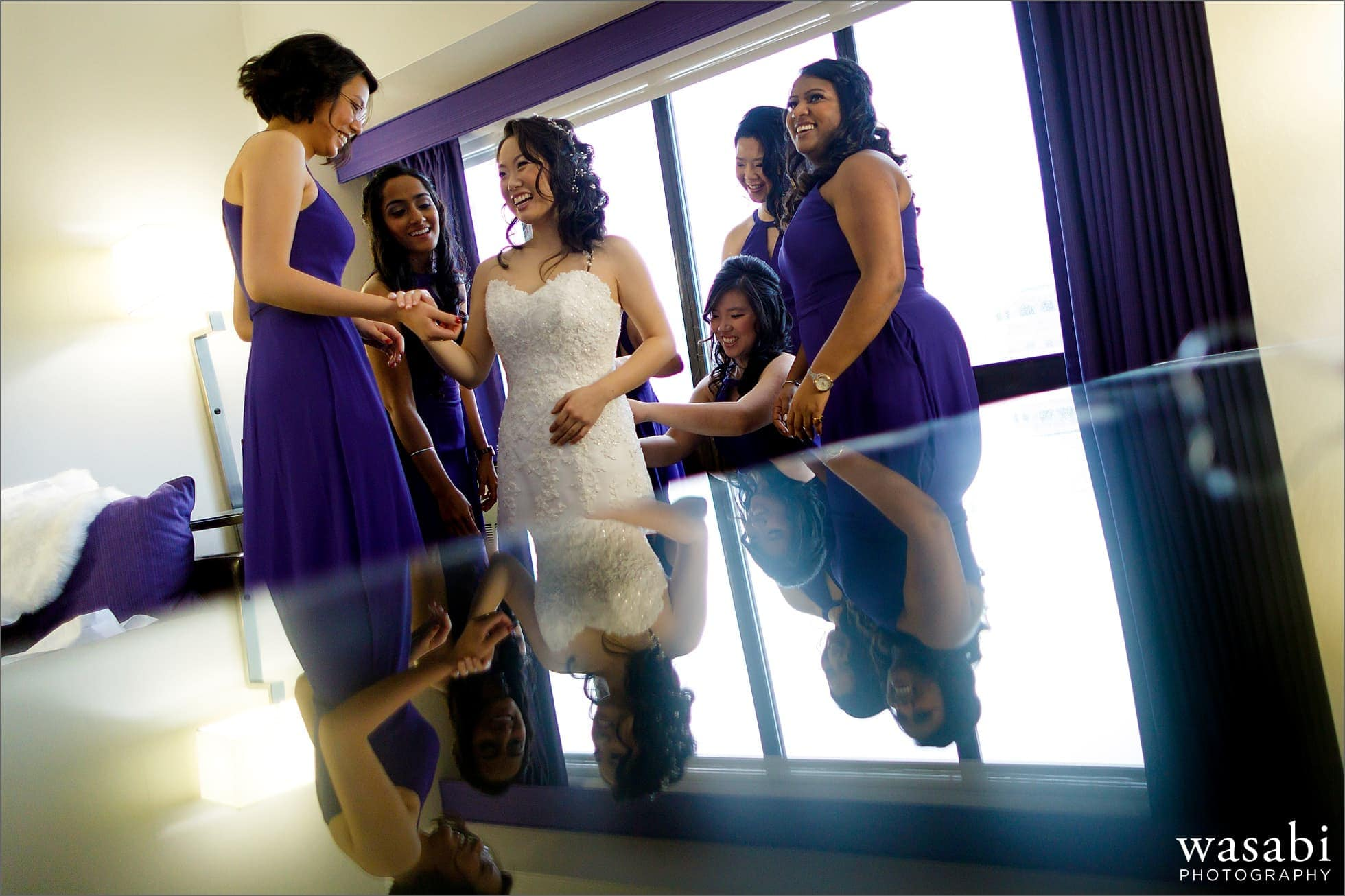 reflection of bridesmaids helping bride get into wedding dress at Holiday Inn Chicago Mart Plaza River North