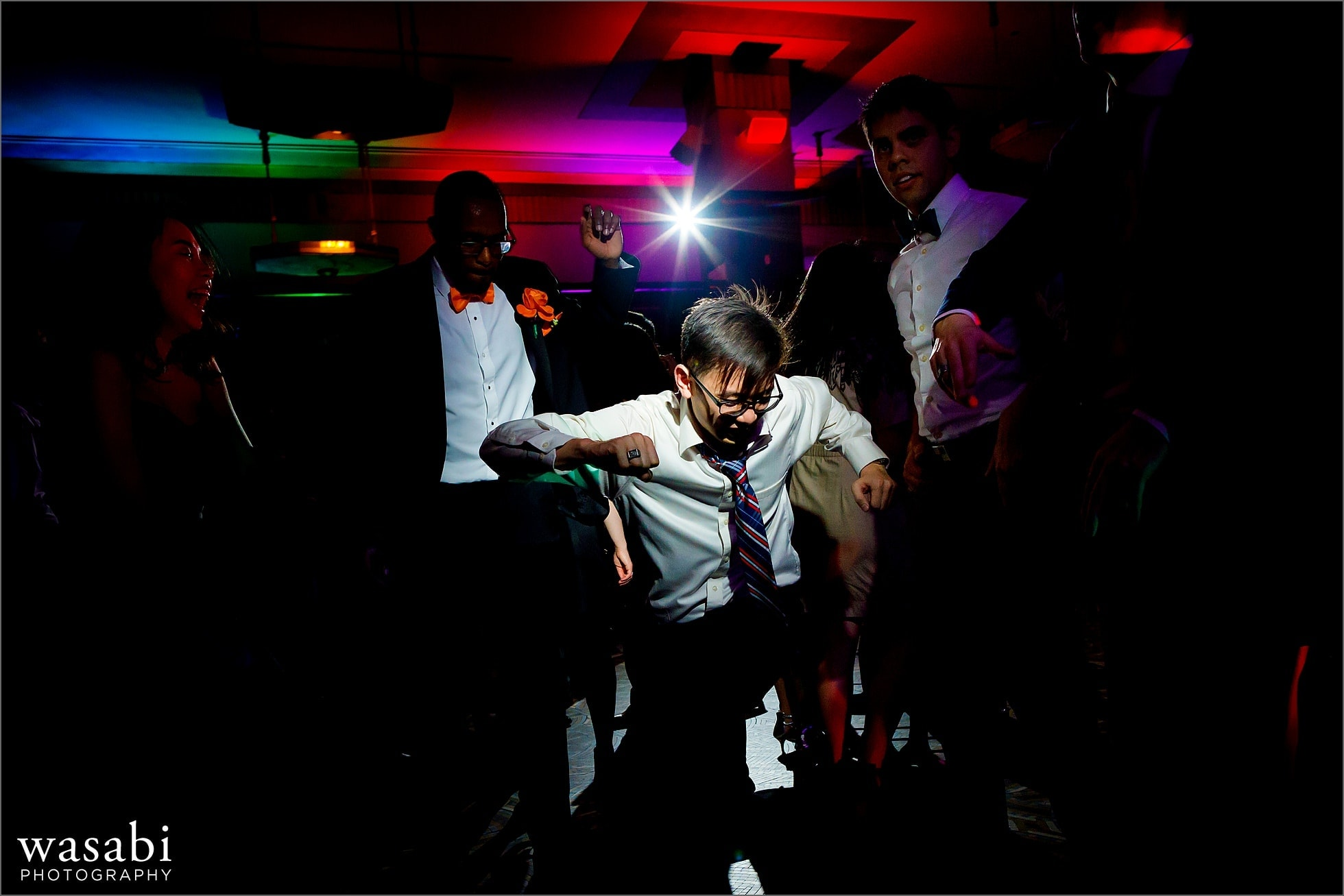 wedding guests on the dance floor with awesome color up lighting during Montgomery Club wedding reception in Chicago