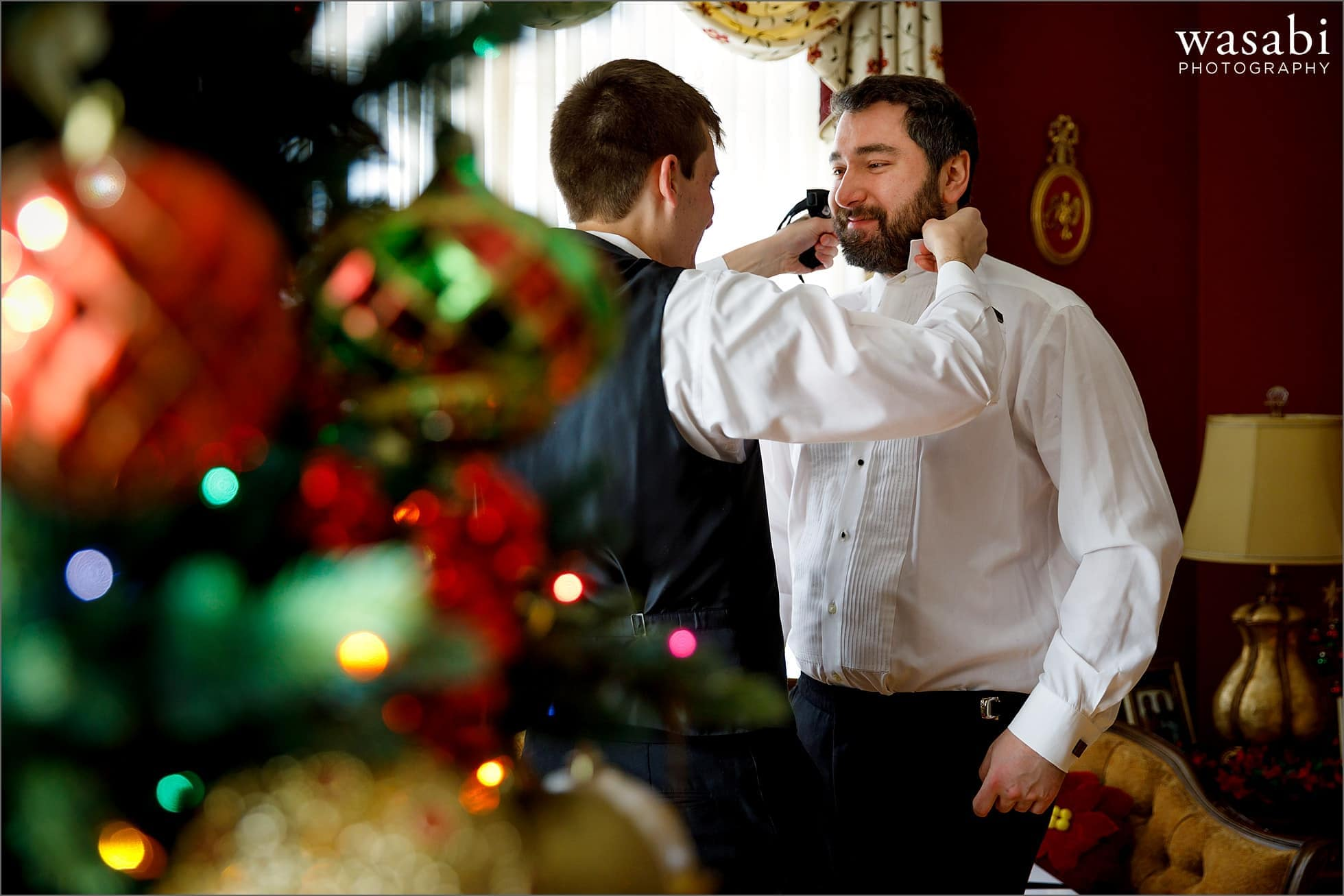 best man helps groom put on tie while getting ready for wedding