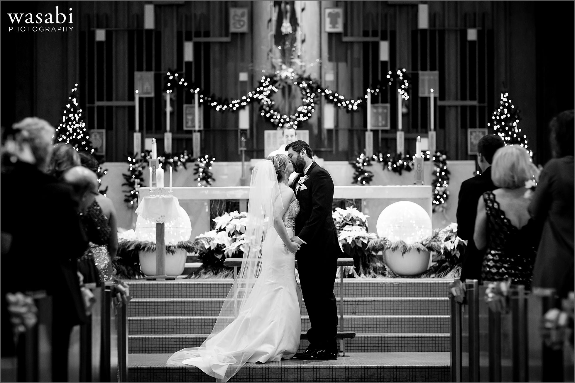 black and white first kiss wide photo during wedding ceremony at Immaculate Conception Catholic Church in Chicago