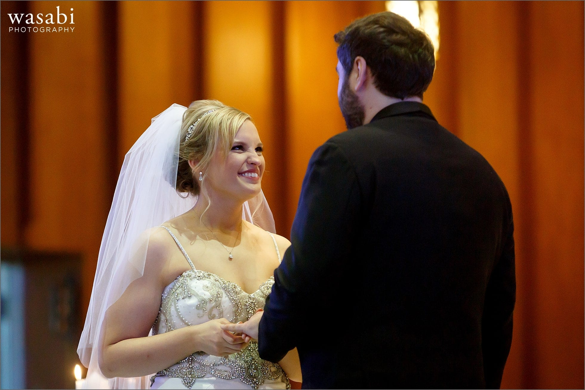 bride and groom exchange rings during wedding ceremony at Immaculate Conception Catholic Church in Chicago
