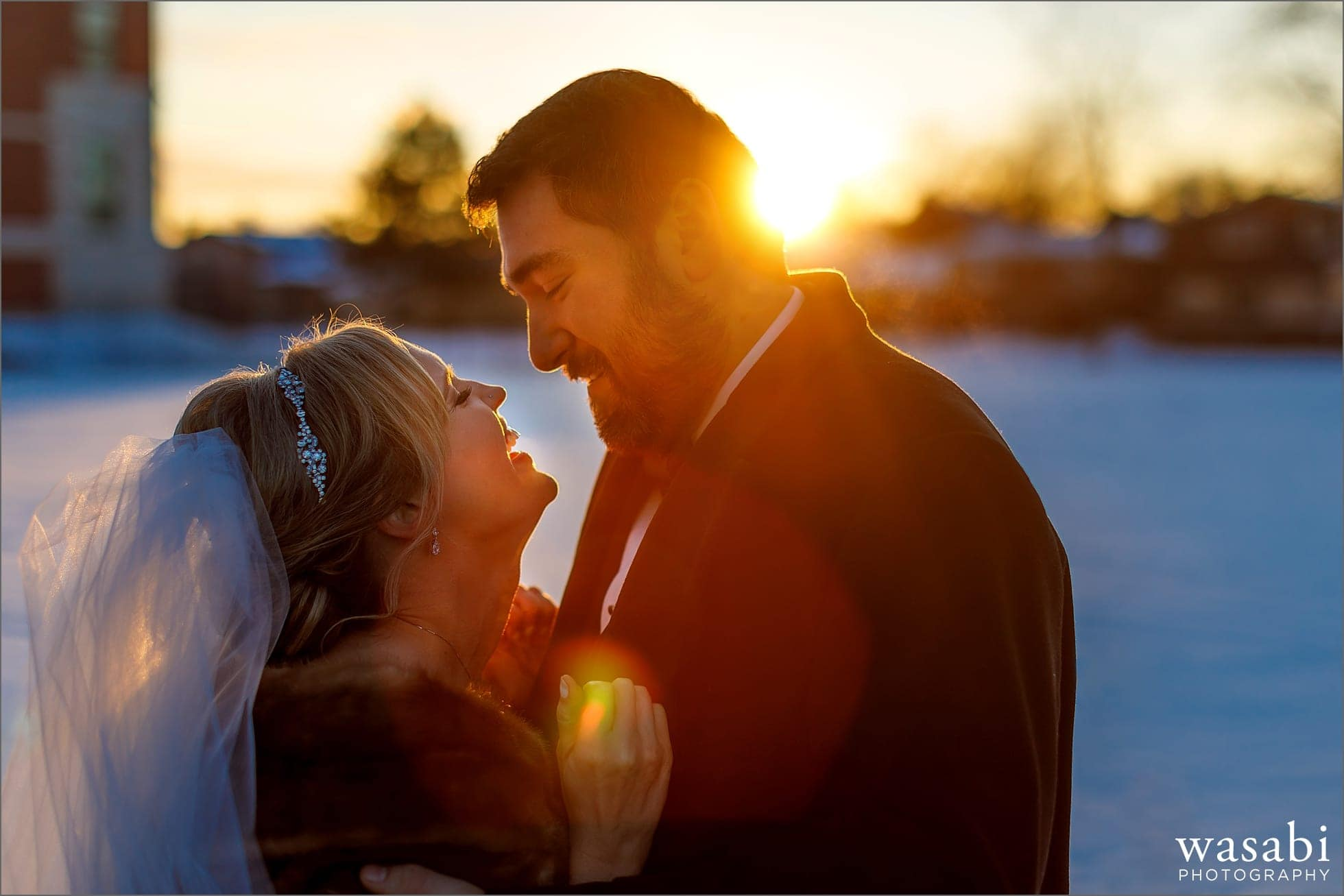bride and groom portrait outside Immaculate Conception Catholic Church in Chicago at sunset with lens flare