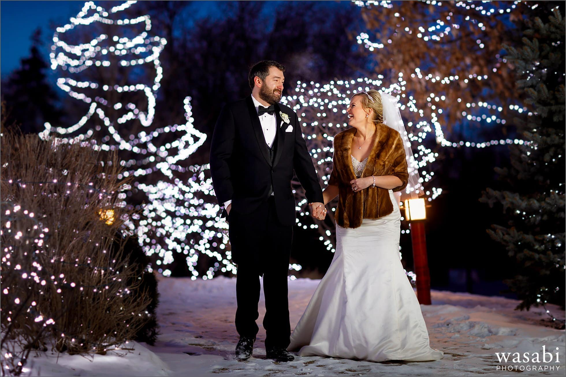 bride and groom portrait walk with christmas lights in the background at Friendship Park in Wheeling