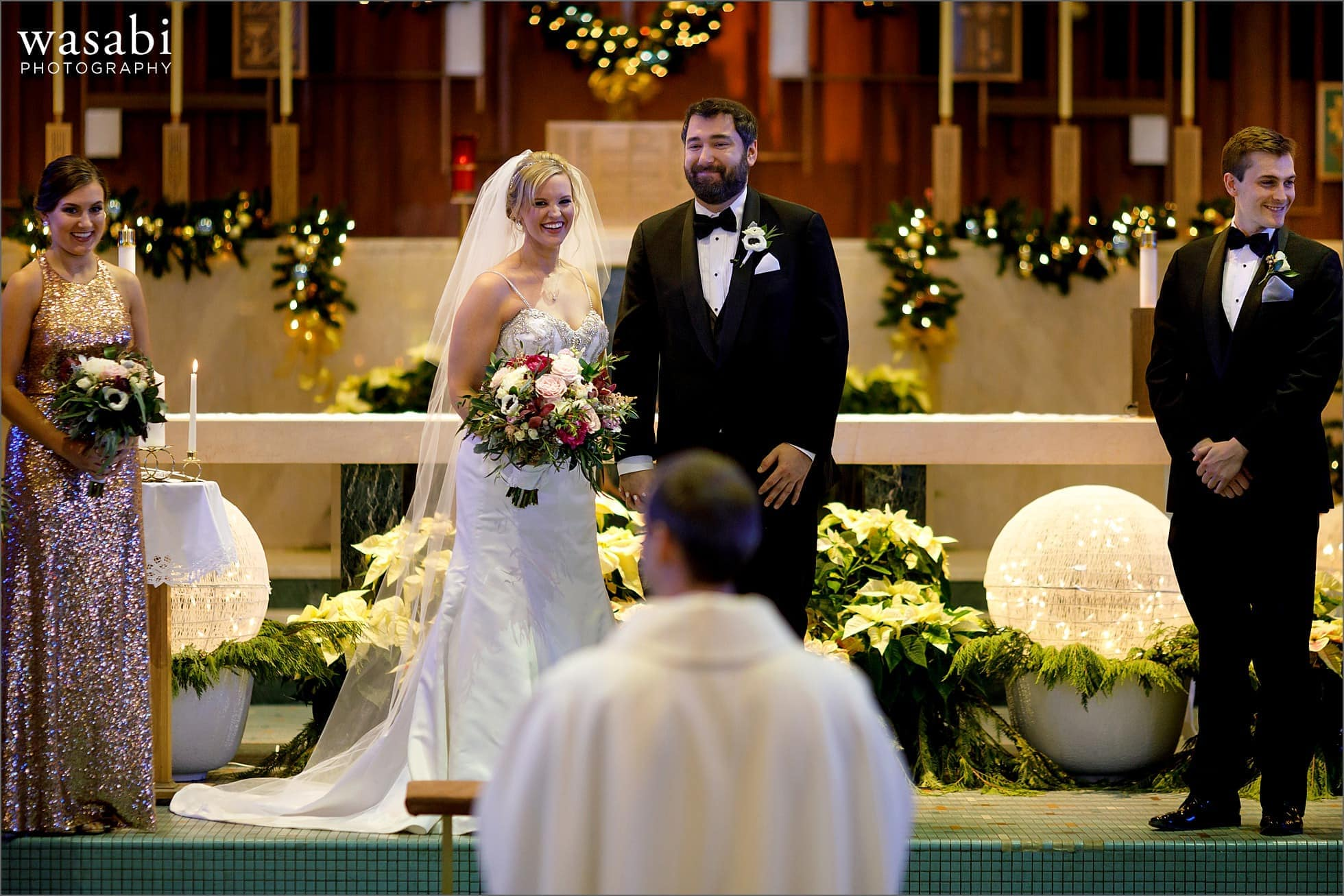 bride and groom smile during wedding ceremony at Immaculate Conception Catholic Church in Chicago