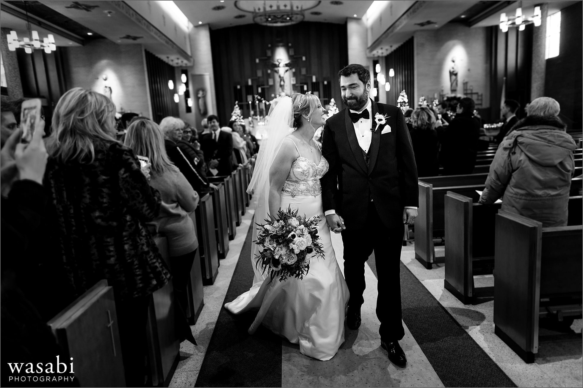 bride and groom walk down the aisle after wedding ceremony at Immaculate Conception Catholic Church in Chicago