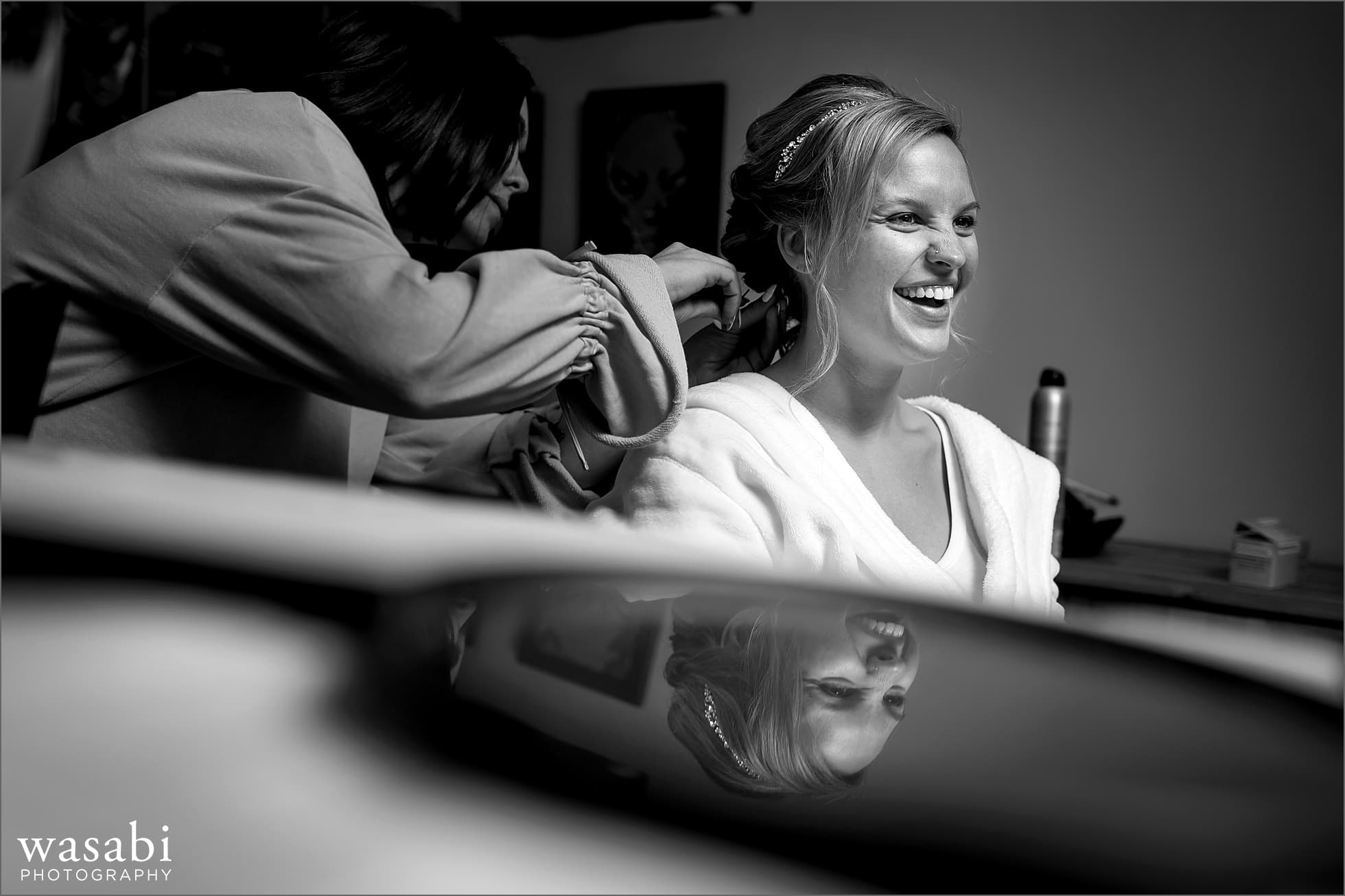 bride has her hair done while getting ready for wedding reflection in mirror