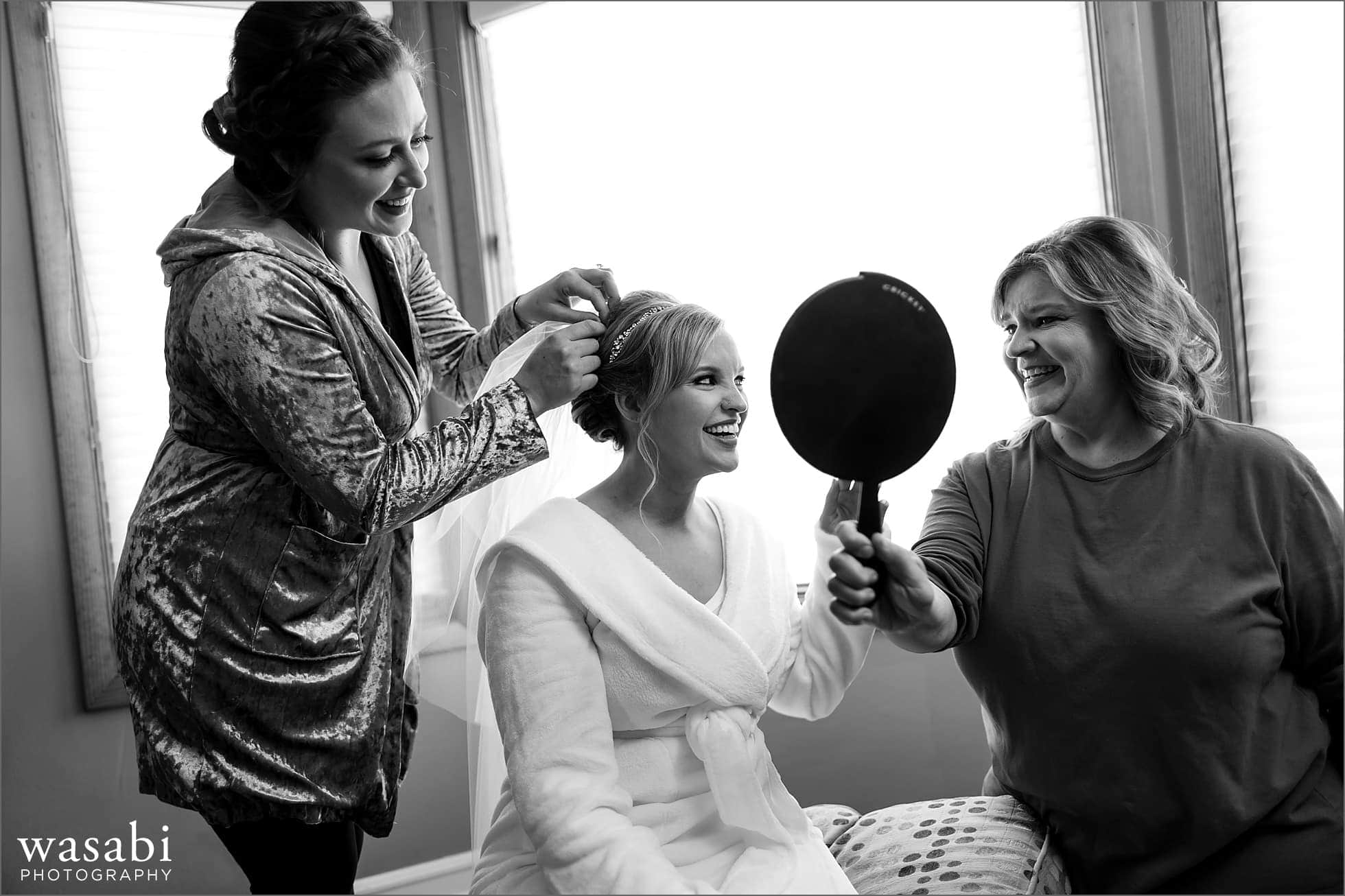 bride has veil put into her hair while getting ready for her wedding