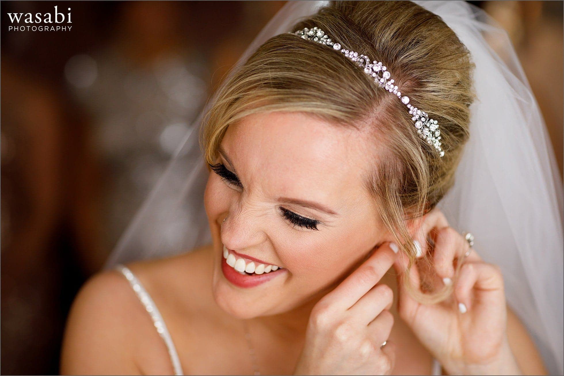 bride puts on earrings while getting ready for wedding