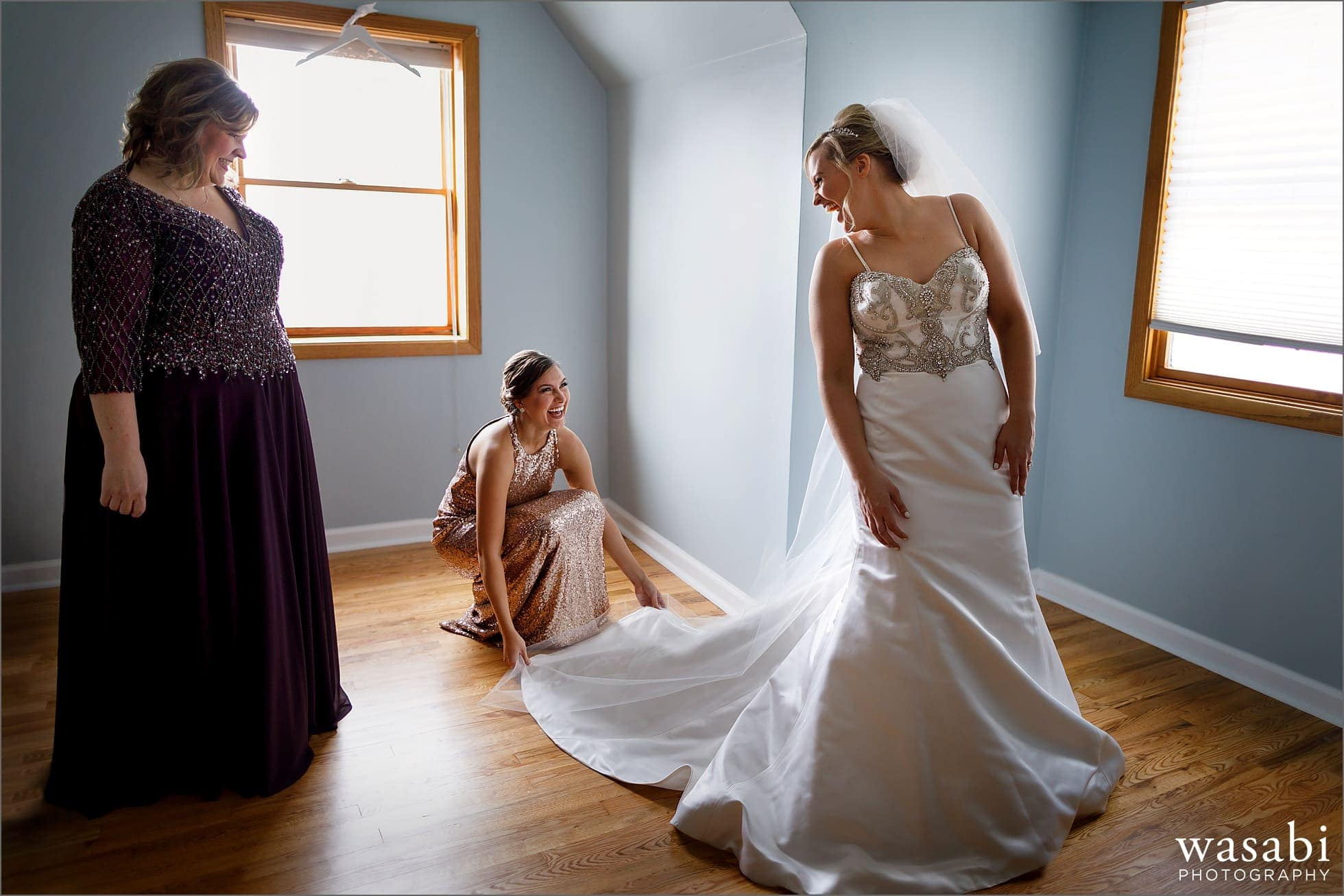 bride steps into dress while bridesmaid helps and mother watches