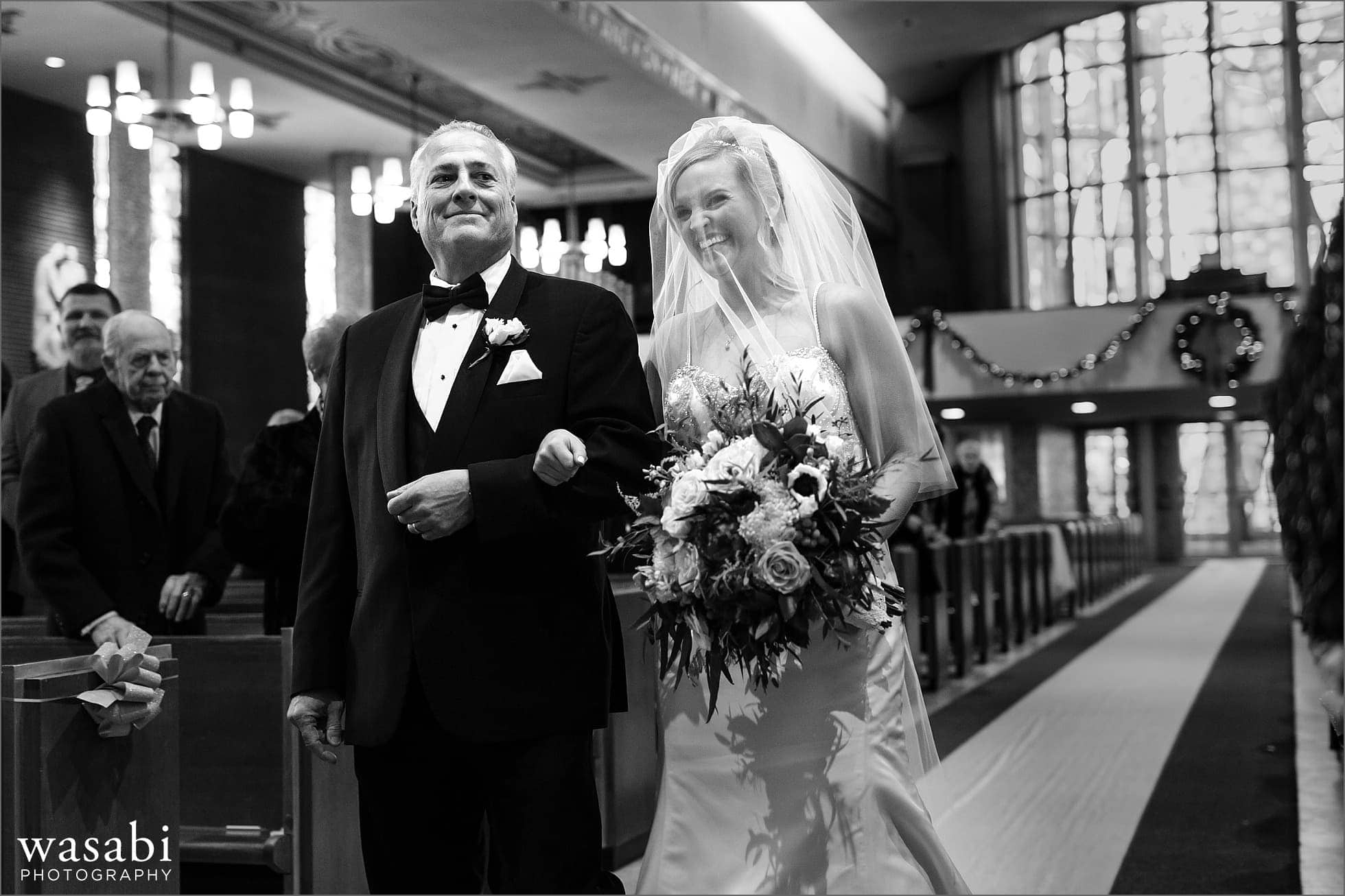 bride walks down the aisle with father during wedding ceremony at Immaculate Conception Catholic Church in Chicago