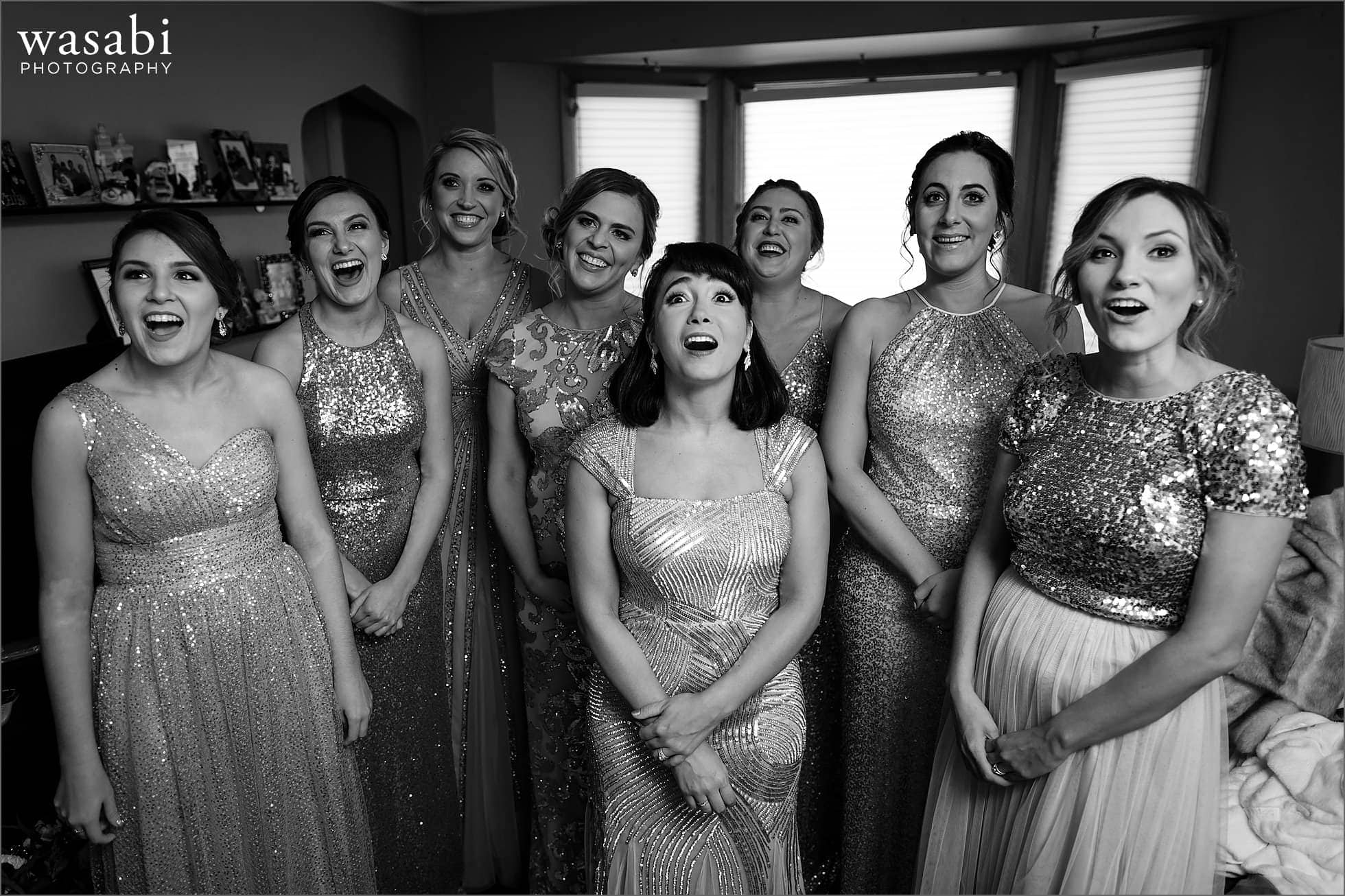 bridesmaids react to seeing bride in wedding dress for the first time as she comes down the stairs
