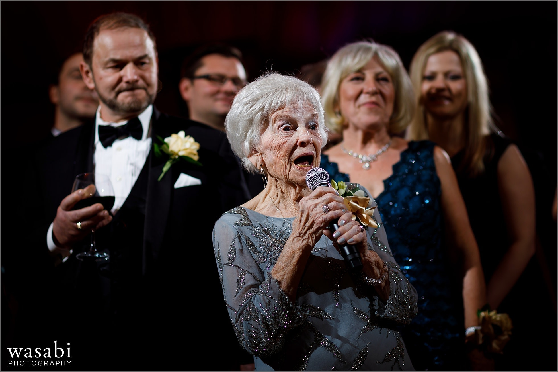 grandmother leads family in sto lat polish song during wedding reception