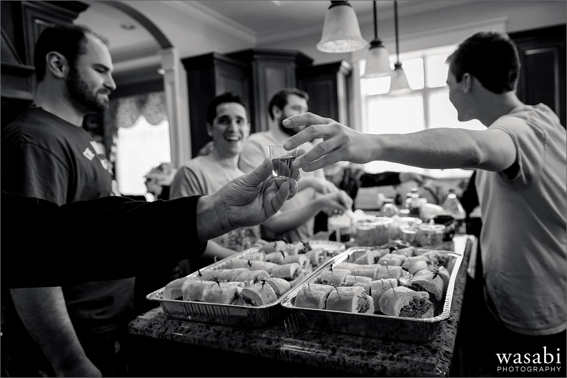 groomsmen pass a shot before a toast while getting ready for a wedding