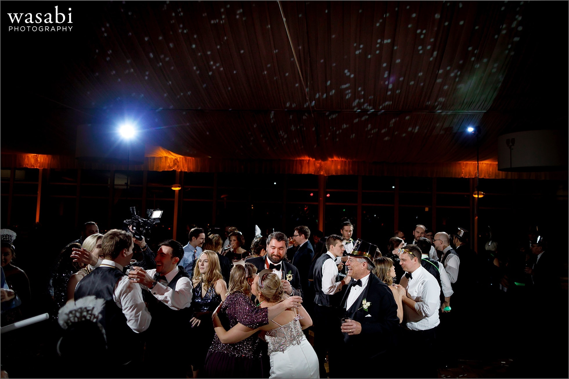wedding guests dancing during New Years Eve wedding reception at Chicago Marriott Lincolnshire Resort with fireworks displayed on ceiling