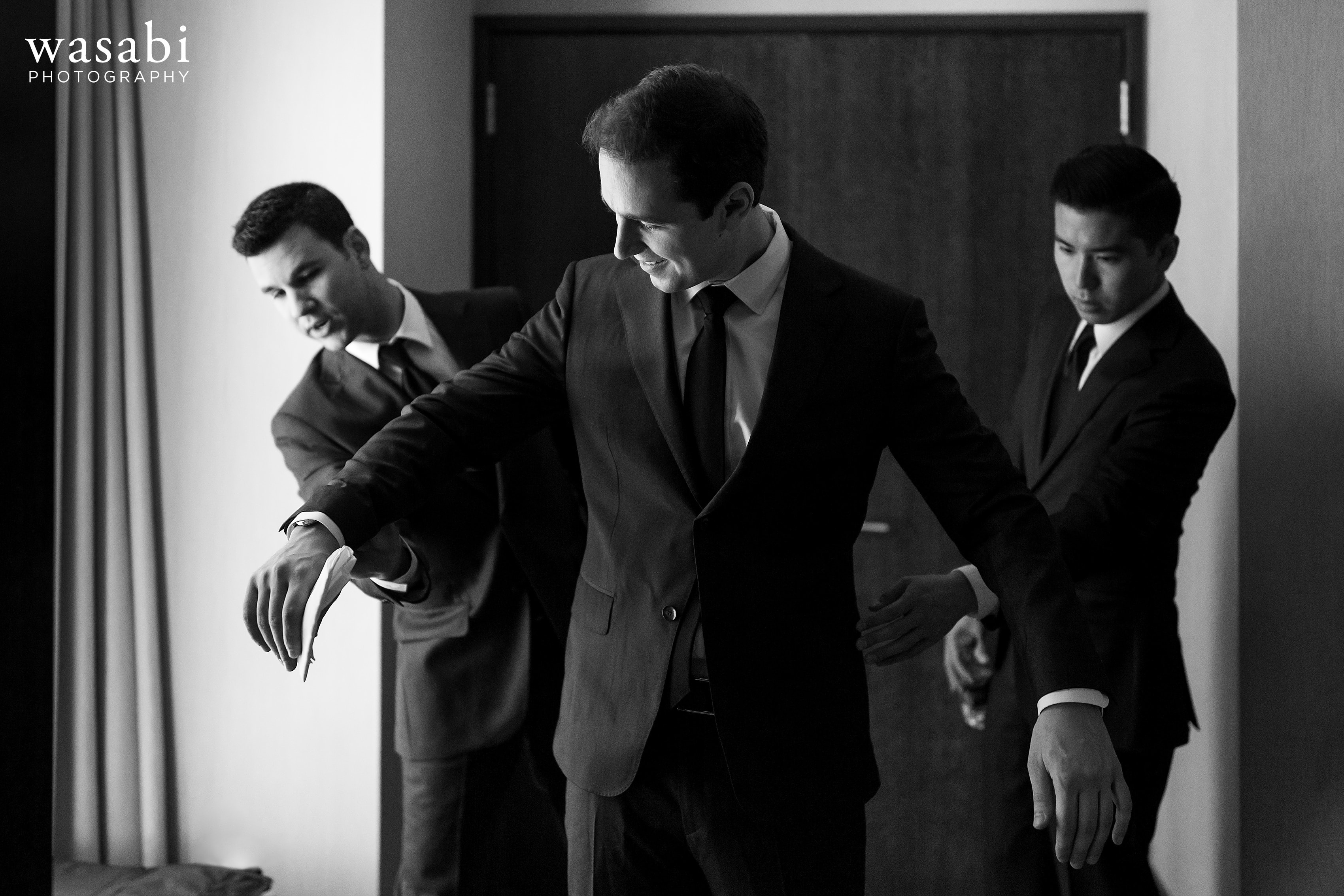 Justin-smiles-as-his-groomsmen-adjust-his-suit-at-Hotel-Palomar-while-getting-ready-for-his-wedding-04
