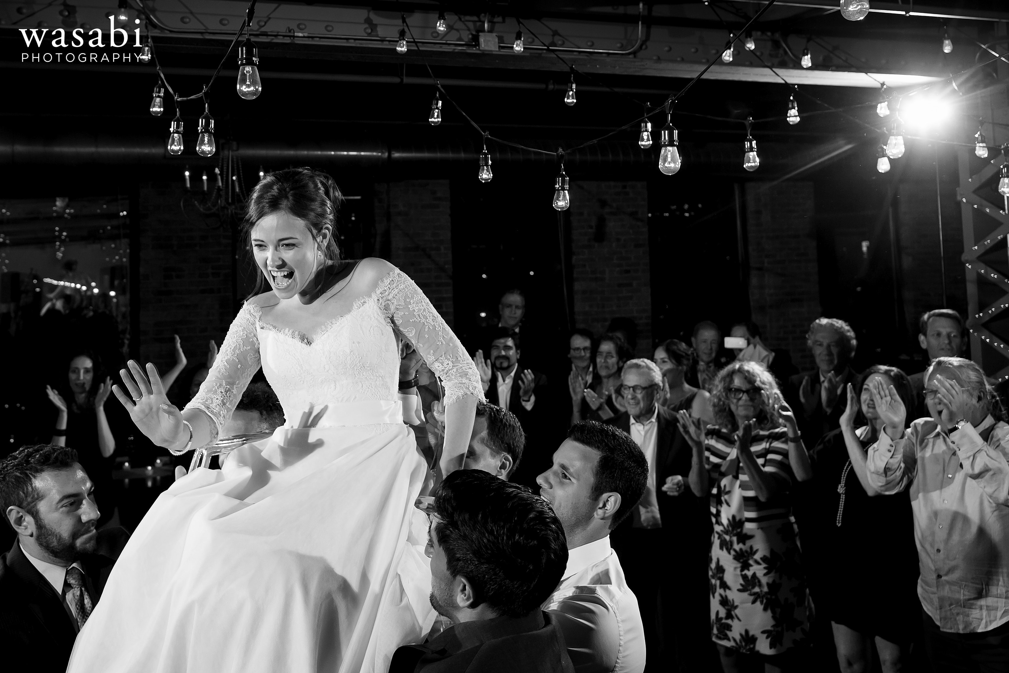 Zoe-&-Justin-are-lifted-on-to-chairs-during-the-hora-at-a-City-View-Loft-Wedding-reception-31
