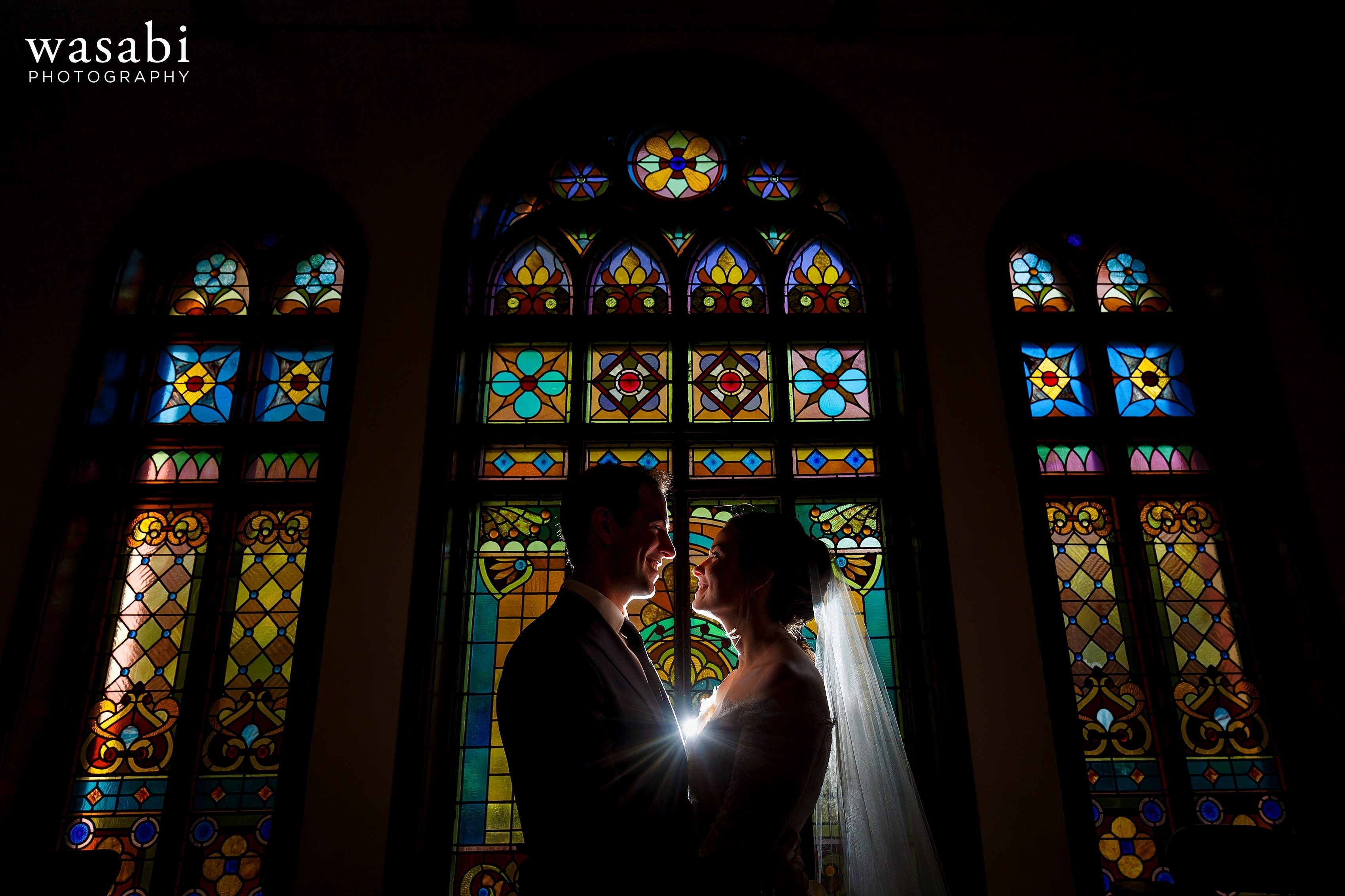 Zoe-and-Justin-pose-for-a-backlit-portrait-in-front-of-the-stained-glass-windows-at-Church-of-Our-Savior-in-Chicago-16