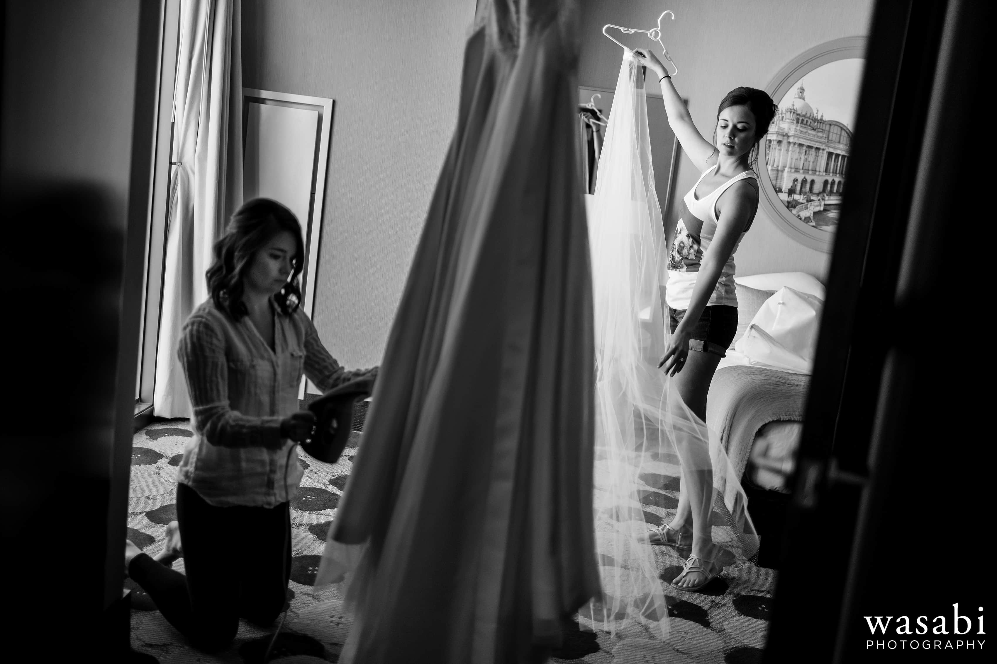 Zoe-straightens-her-vail-while-a-bridesmaid-steams-the-dress-while-getting-ready-at-Hotel-Palomar-in-Chicago-05