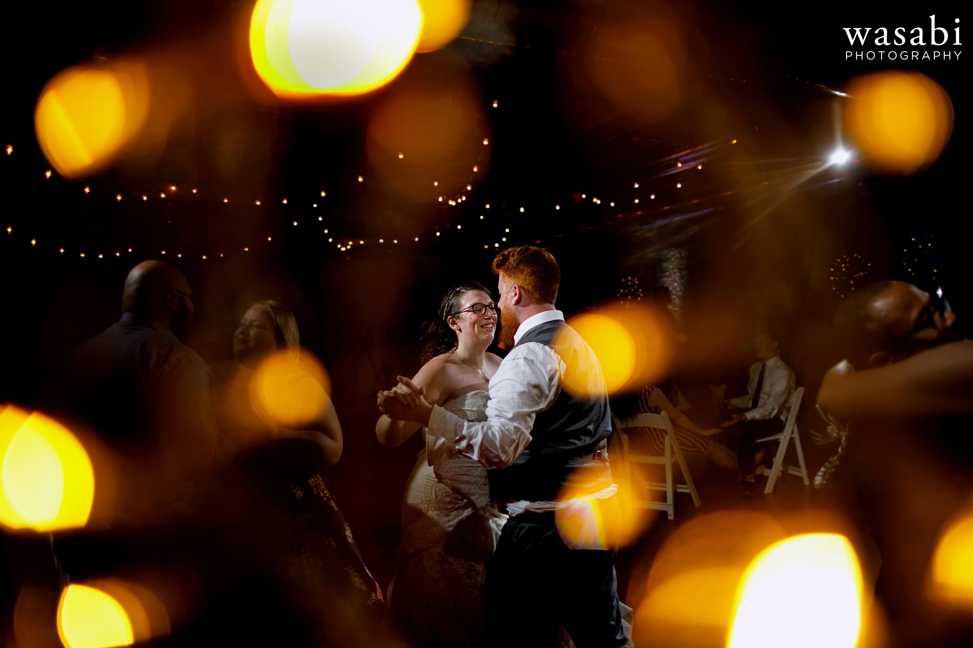 A bride and groom dance with guests during their Loft on Lake wedding reception