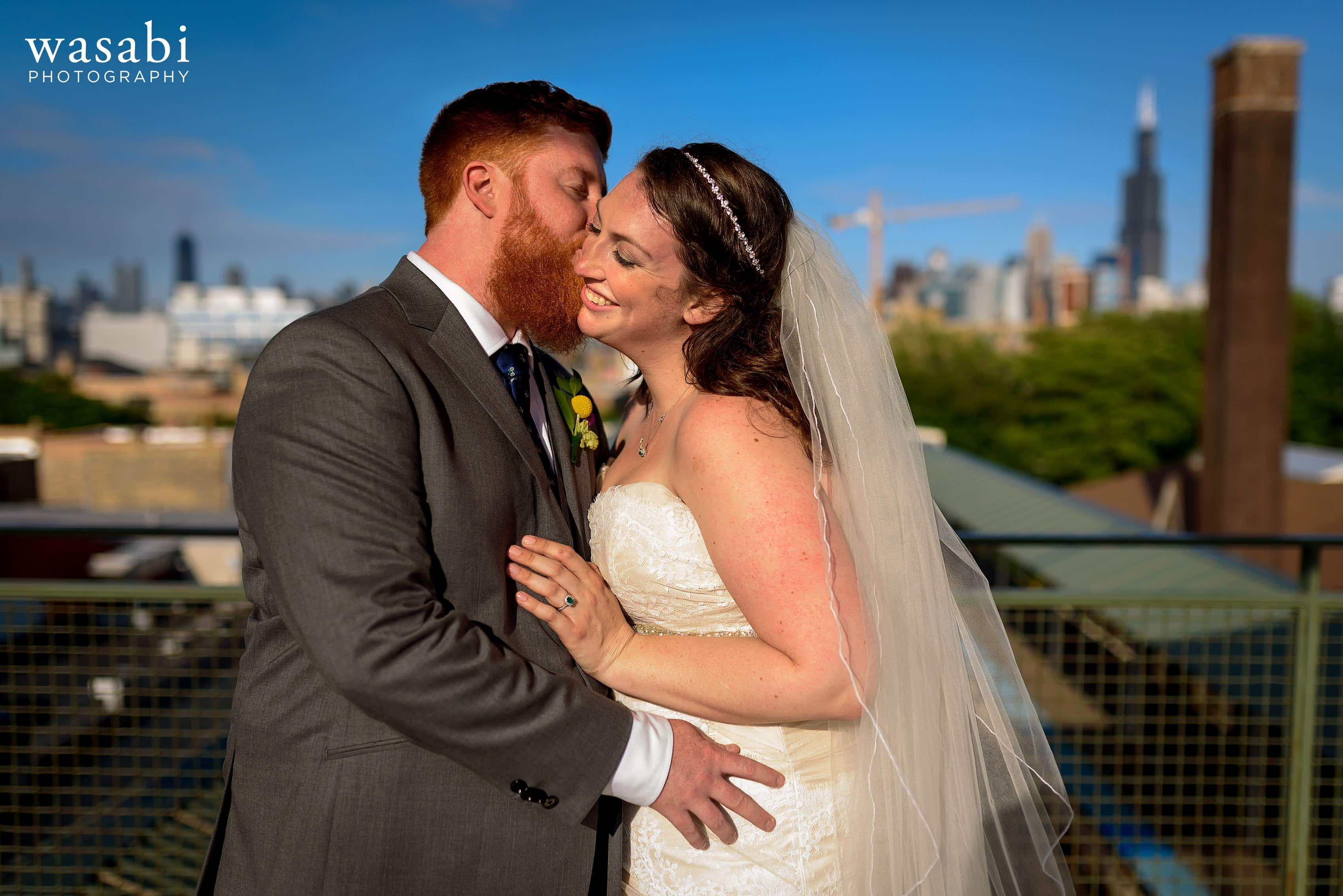 A bride and groom pose for a portrait at the Ashland Green Line Station in Chicagos West Loop neighborhood after their Loft on Lake wedding