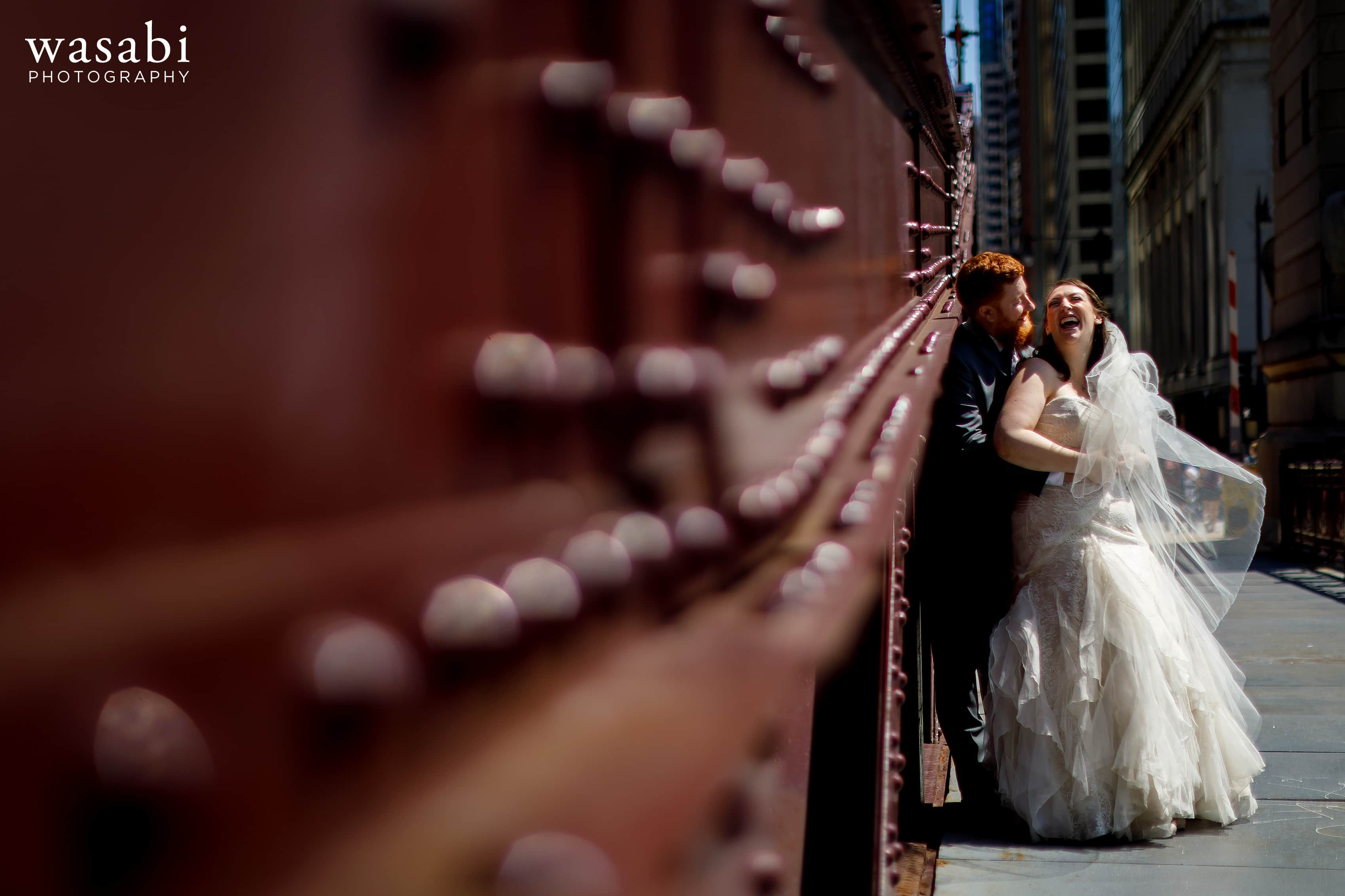 A bride and groom pose for a portrait on the La Salle Street Bridge in Chicago