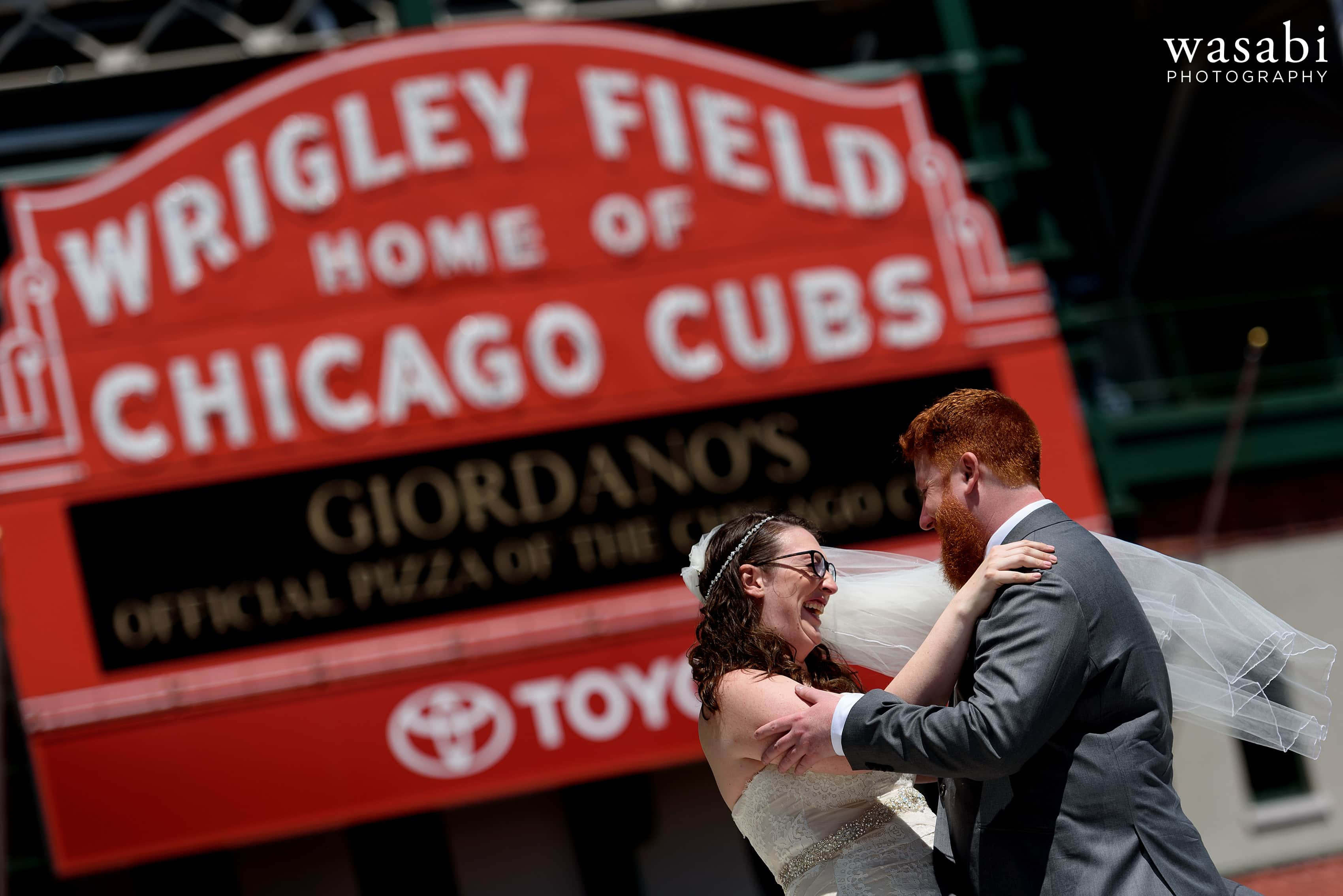 A bride and groom pose for a wedding photo in front of the Wrigley Field marquee sign on their wedding day