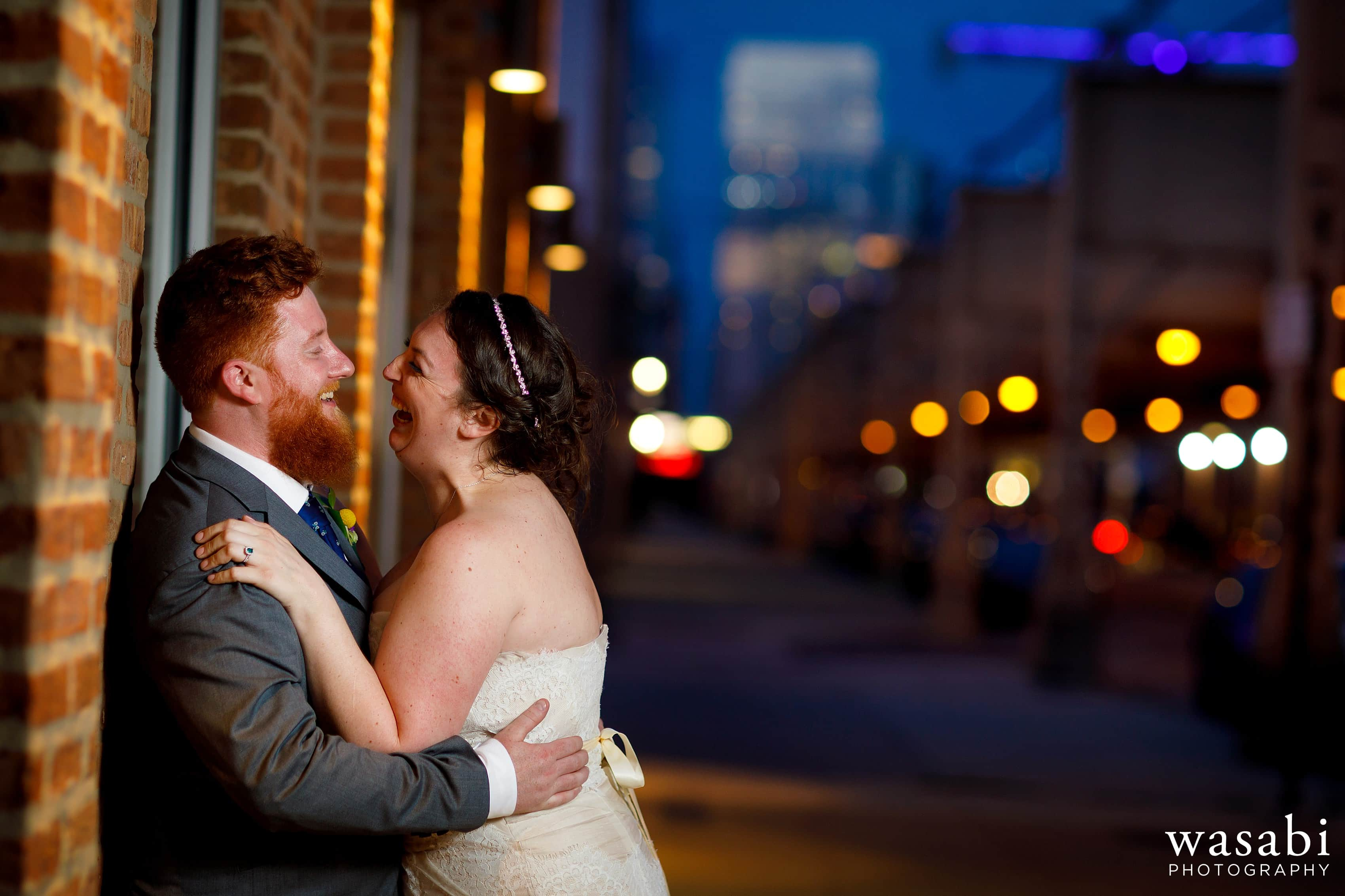 A bride and groom pose for an evening portrait outside their Loft on Lake wedding reception
