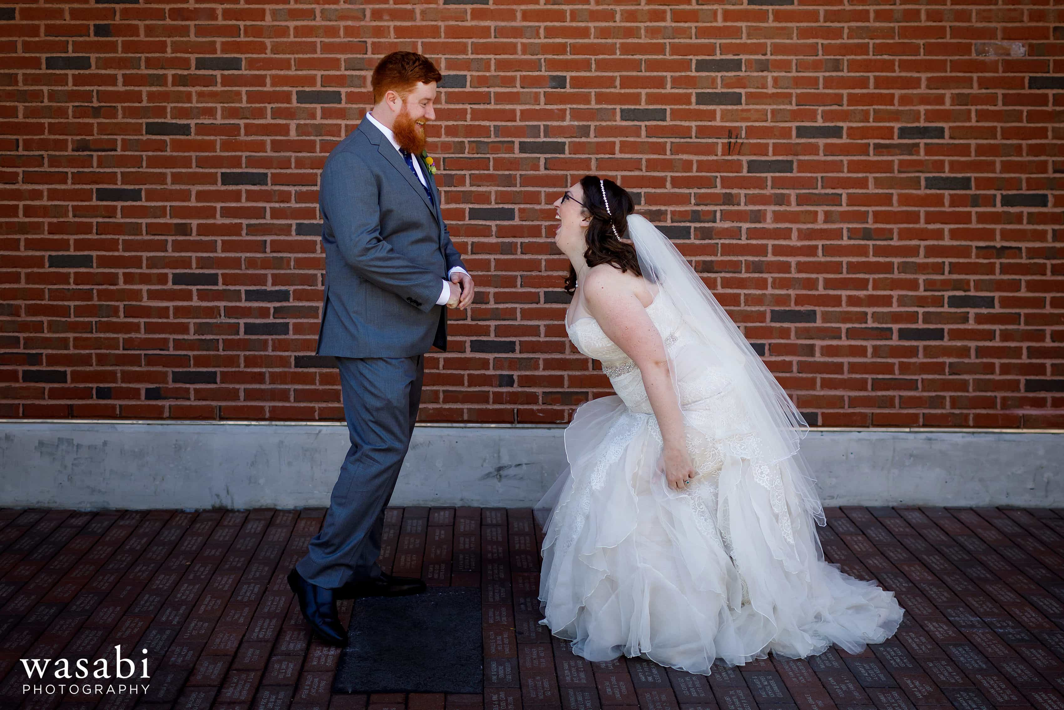 A bride and groom react with a huge expressions during a first look behind the bleachers at Wrigley Field in Chicago