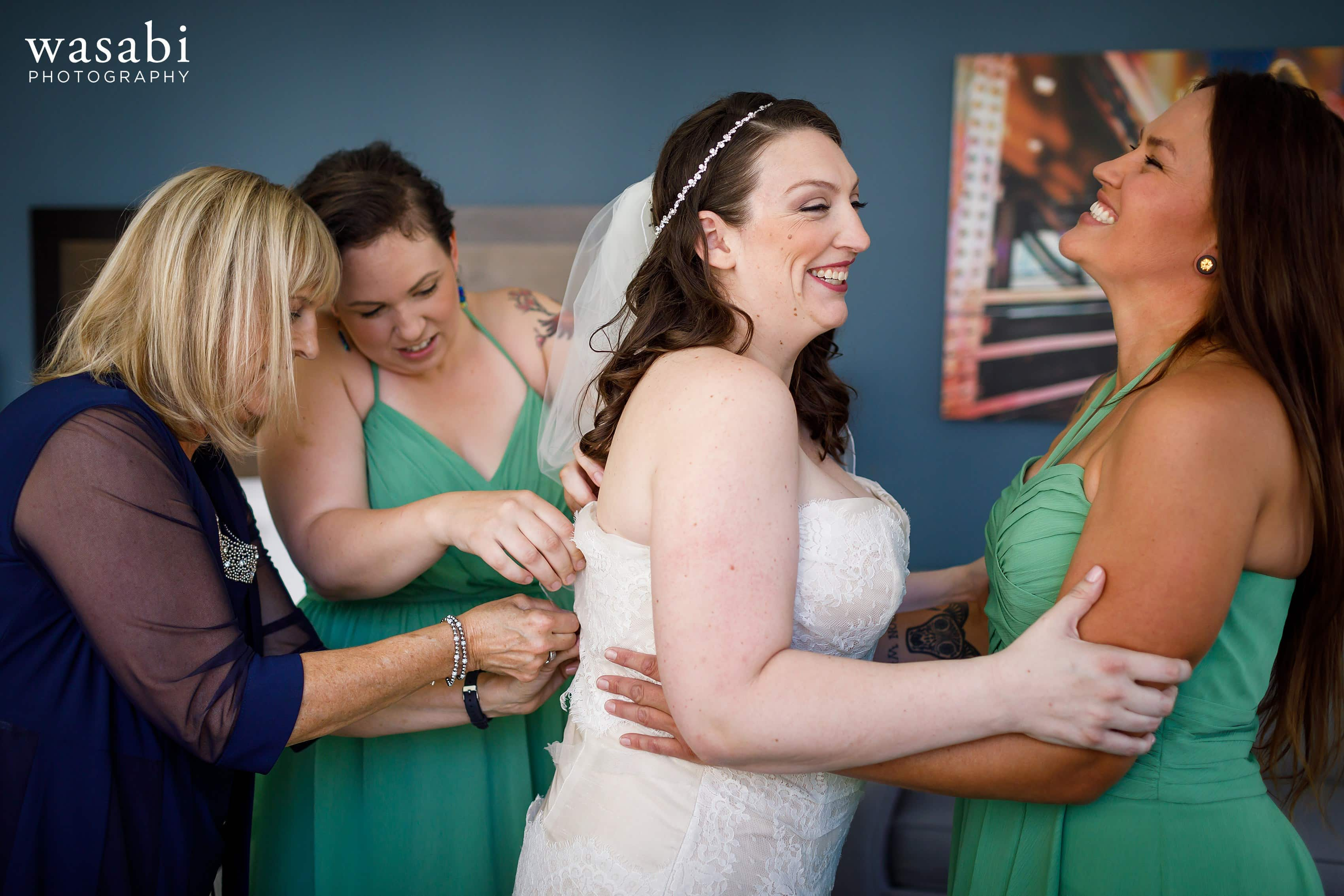 A bride gets into her dress with her mother and bridesmaids while getting ready for her wedding at La Quinta Inn & Suites in downtown Chicago
