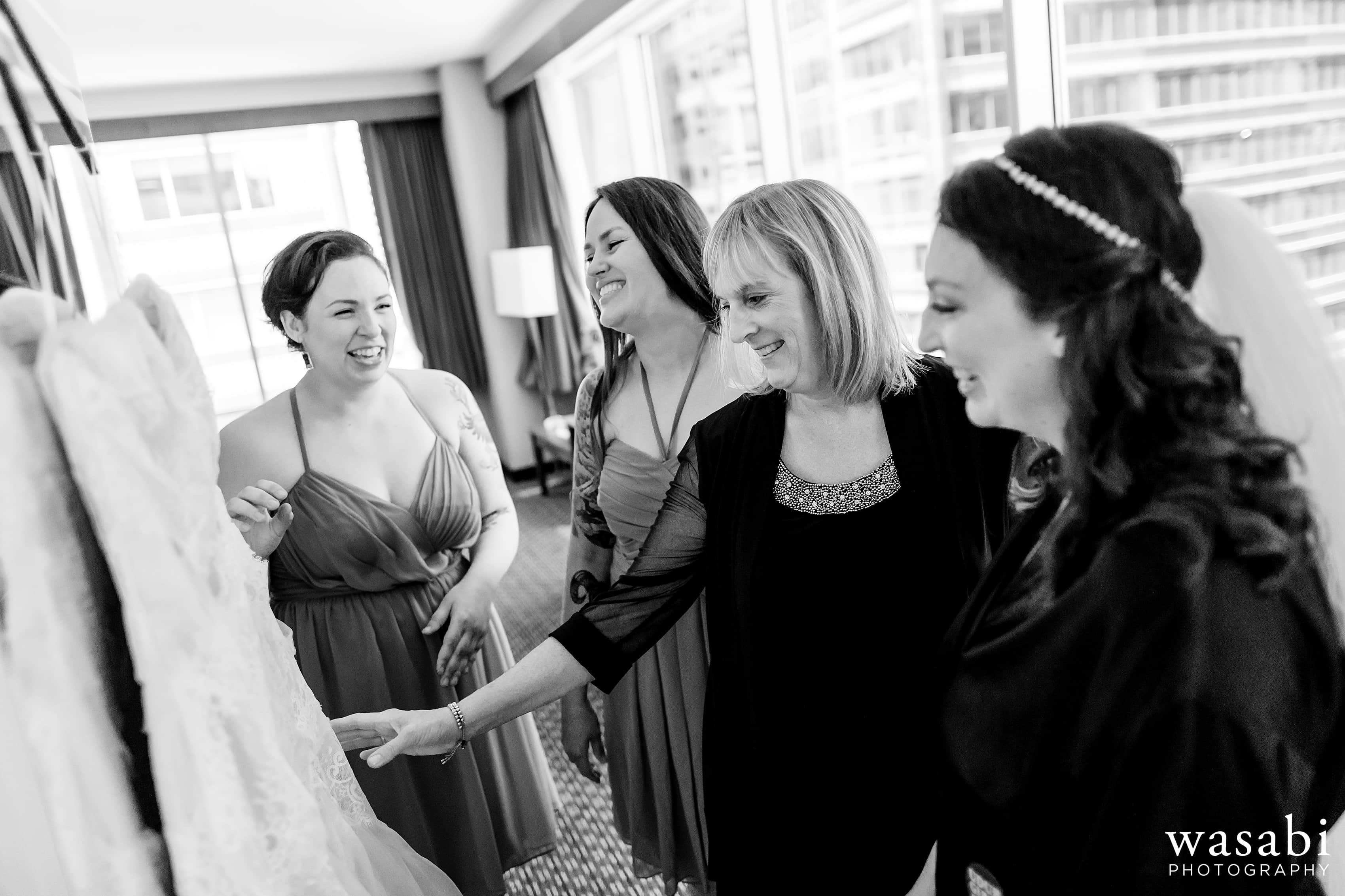 A bride looks at dress with her mother and bridesmaids while getting ready for her wedding at La Quinta Inn & Suites in downtown Chicago