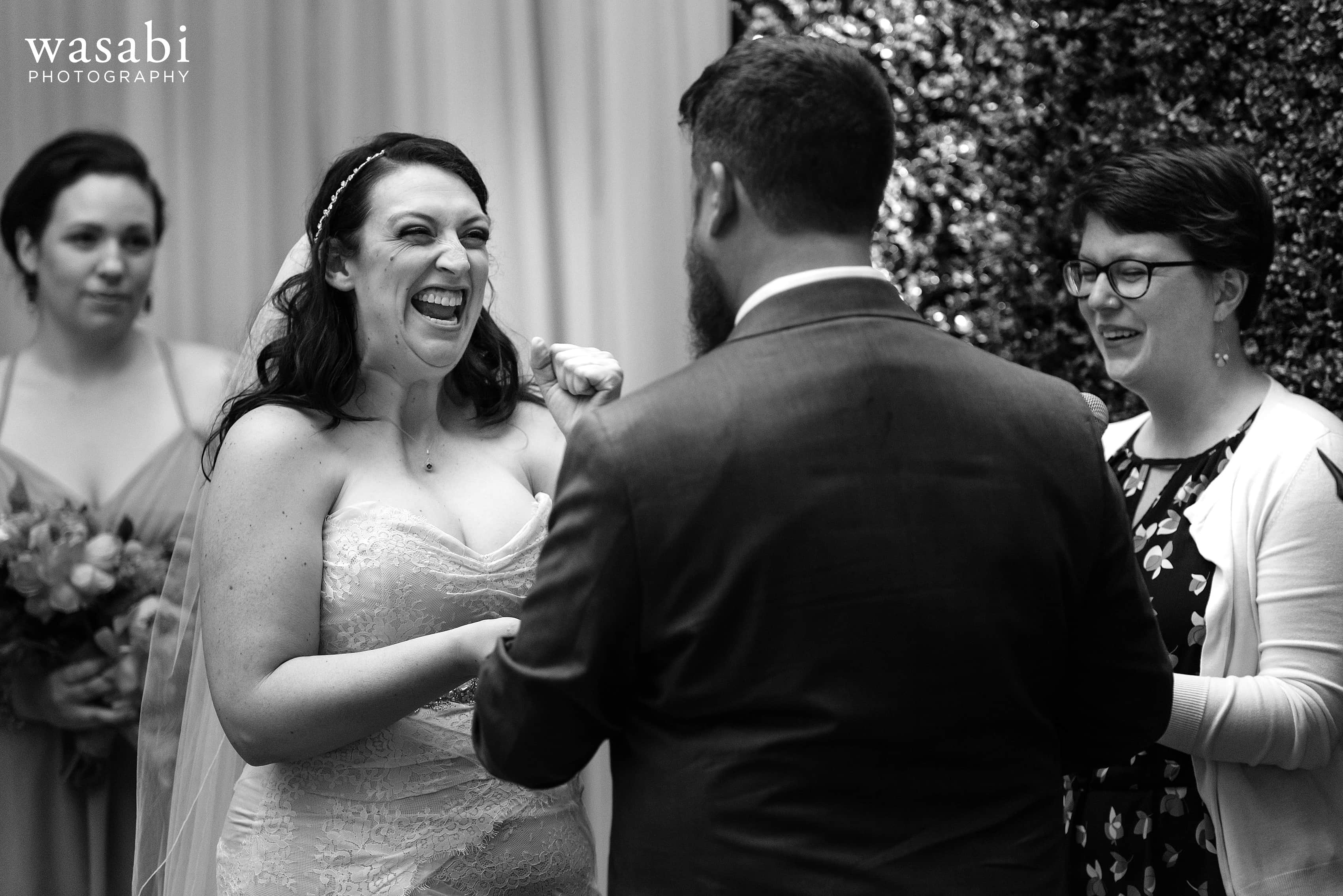 A bride reacts during her vows at her wedding ceremony at Loft on Lake in Chicago
