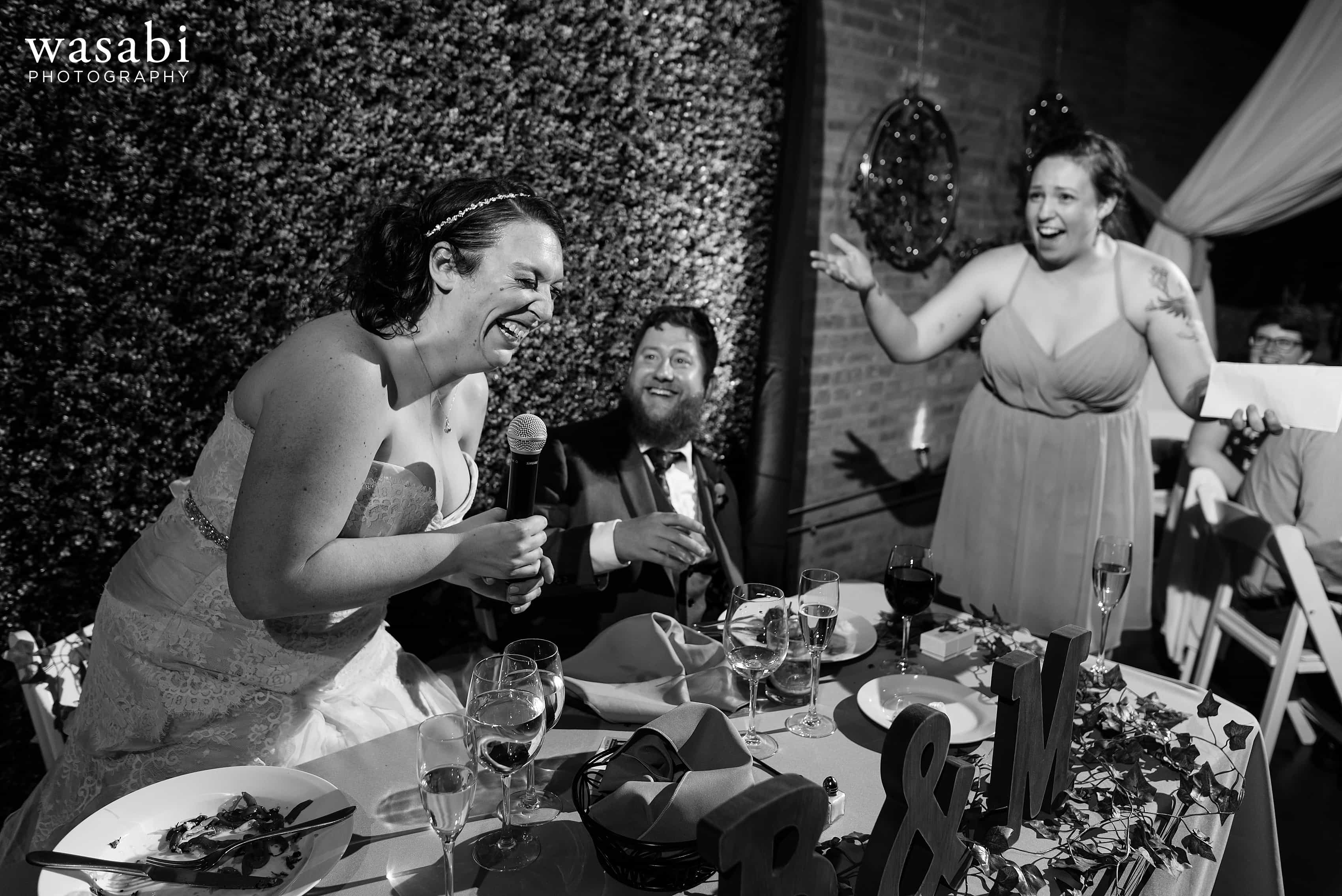 A bride steals the microphone during toasts at a Loft on Lake wedding reception