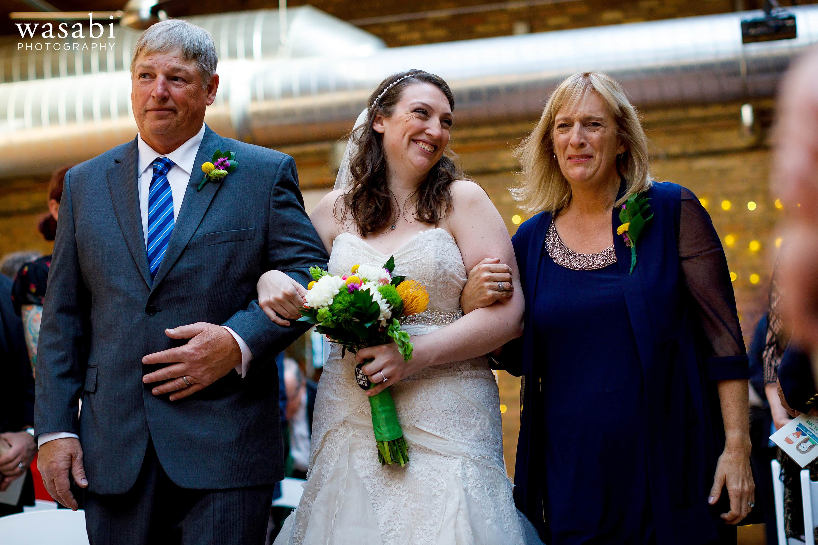 A bride walks down the aisle with her parents during a wedding ceremony Loft on Lake in Chicago