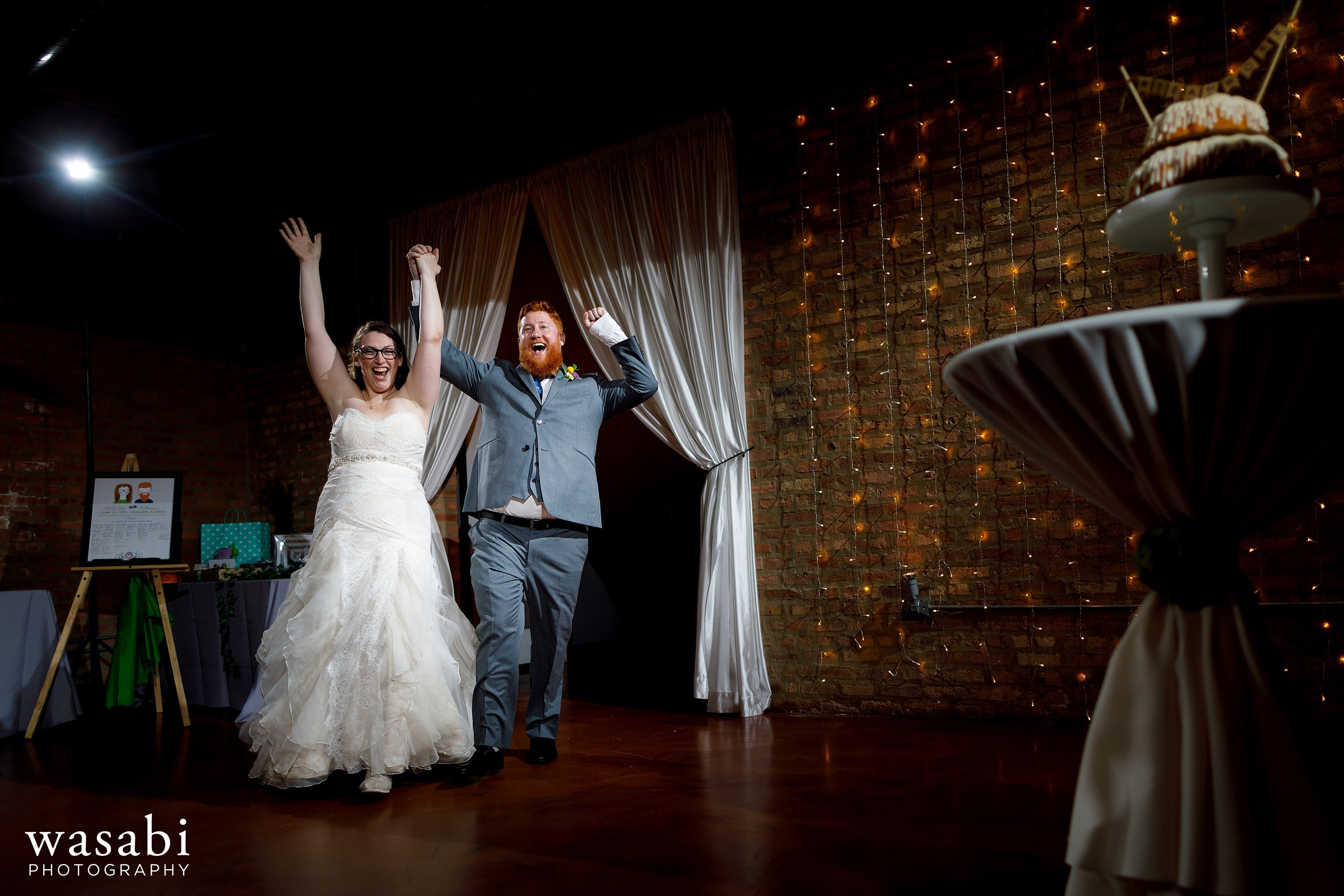 A couple walks into their Loft on Lake wedding reception