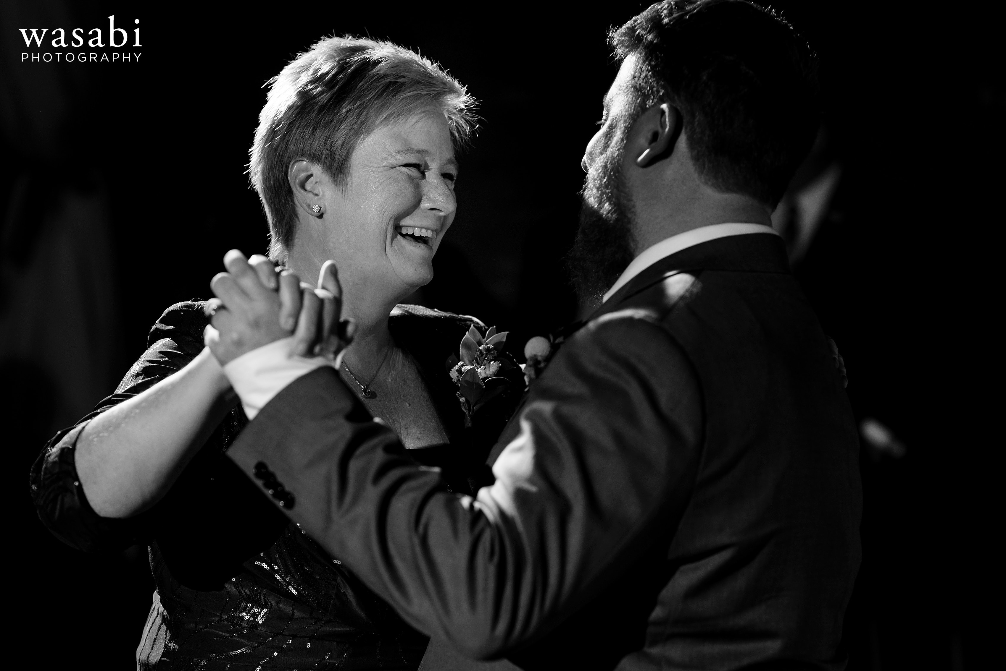 A groom dances with her son during first dances at a Loft on Lake wedding reception