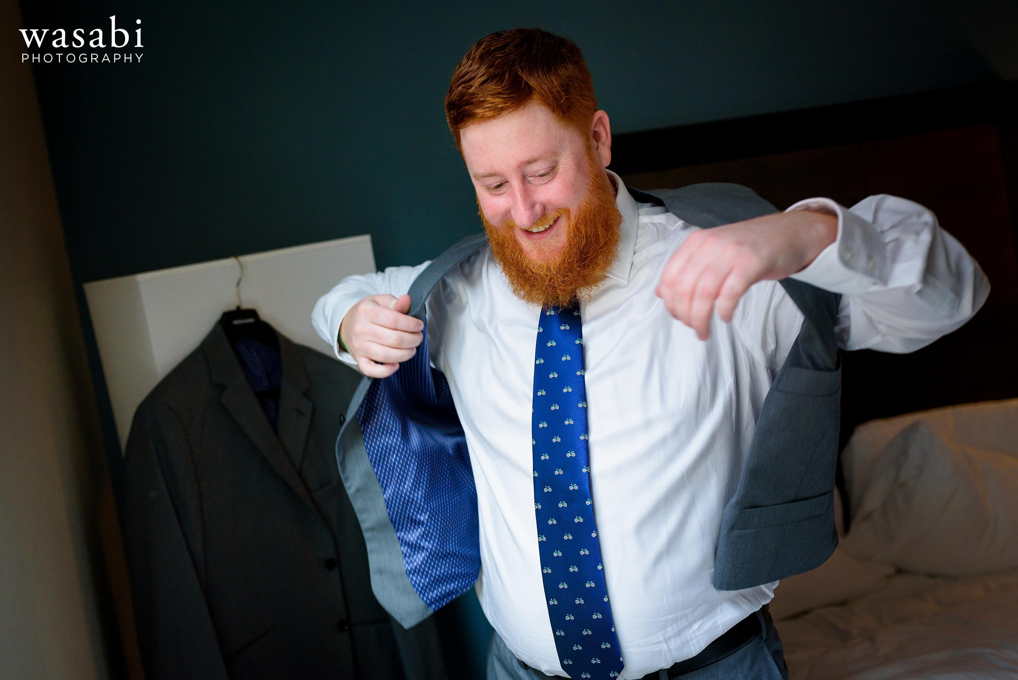 A groom puts on his vest his ties while getting ready for his wedding at La Quinta Inn & Suites in downtown Chicago