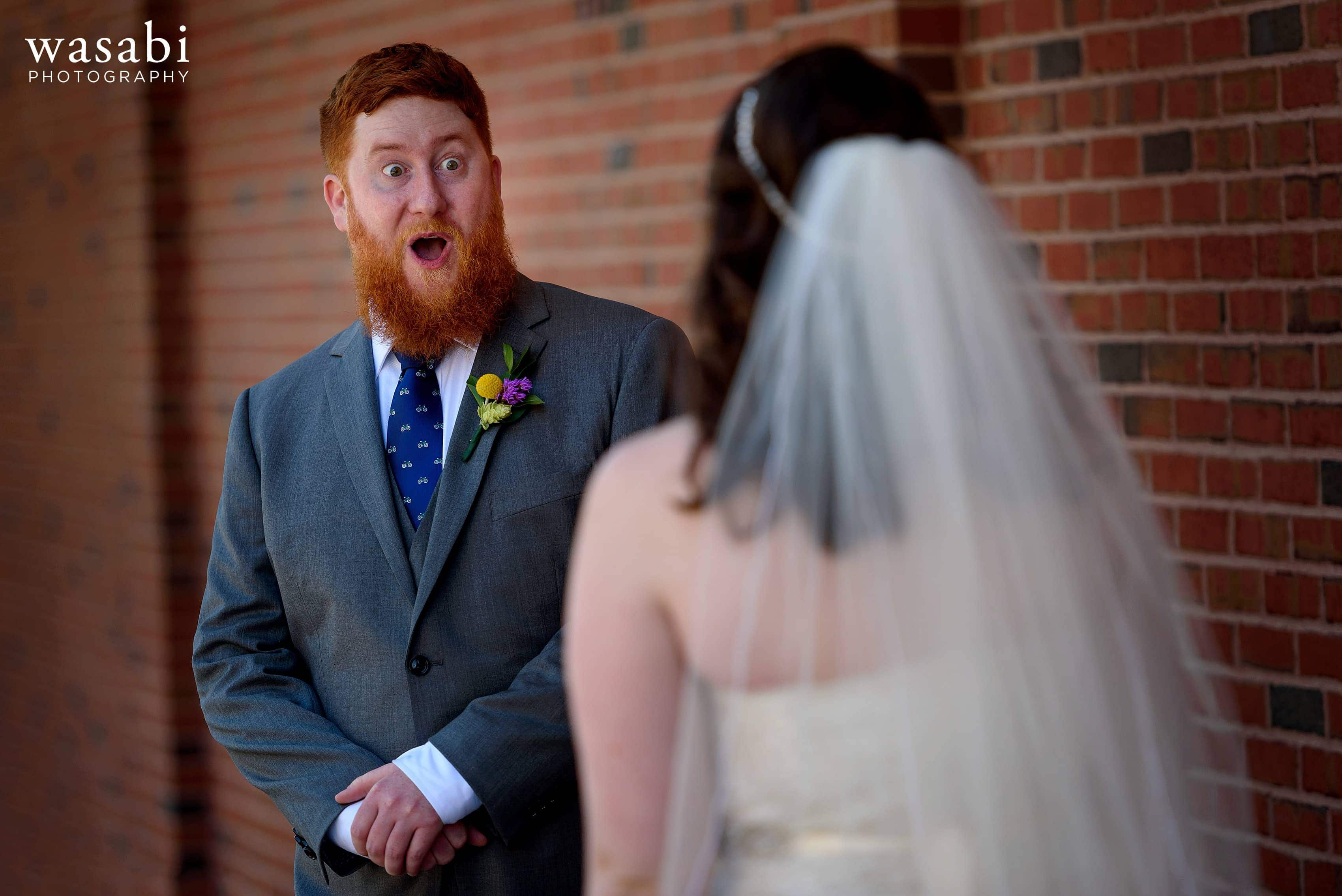 A groom reacts with a huge wide-eyed expression during a first look behind the bleachers at Wrigley Field in Chicago