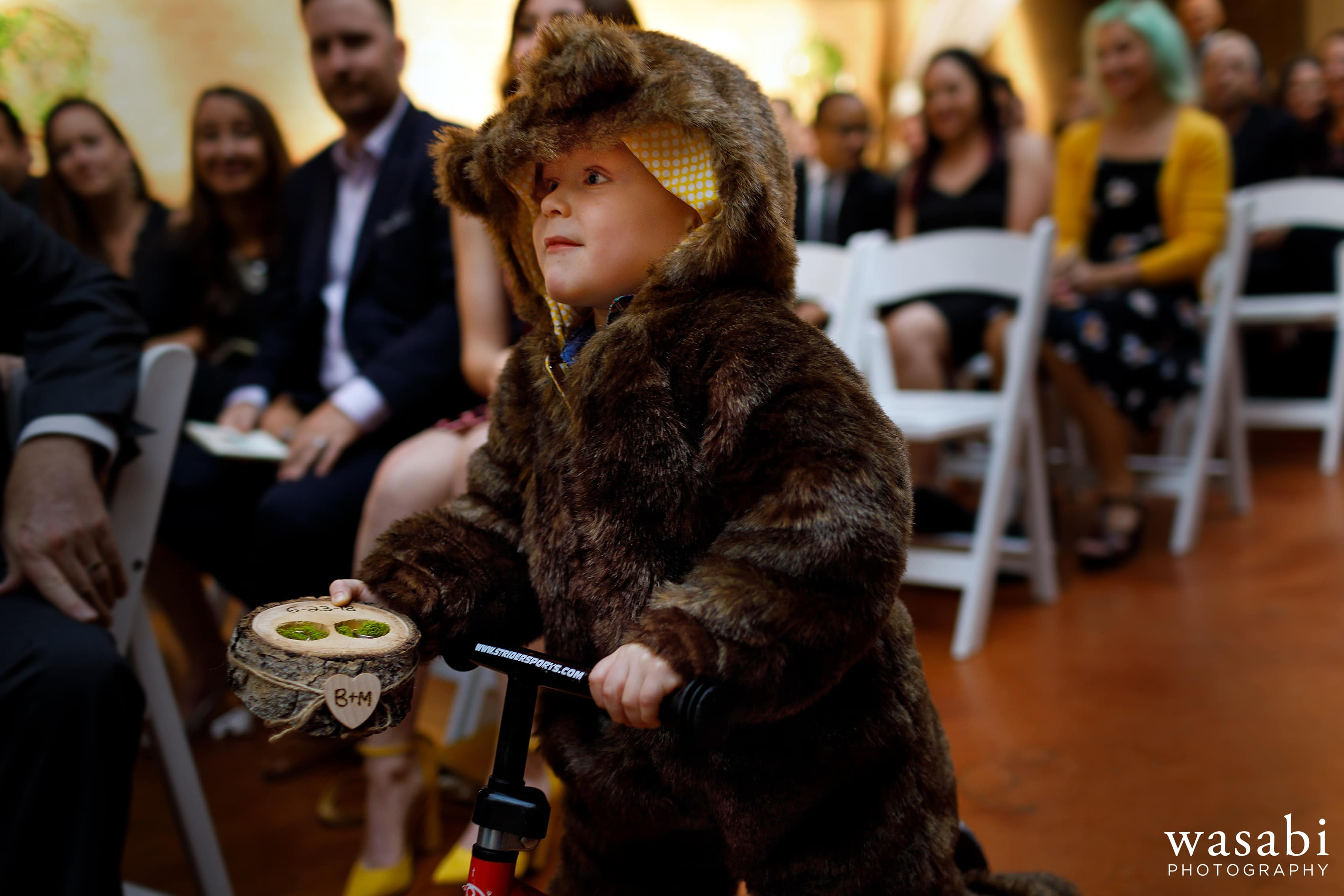 A ring bear rides his bike down the aisle to deliver the rings during a wedding ceremony Loft on Lake in Chicago