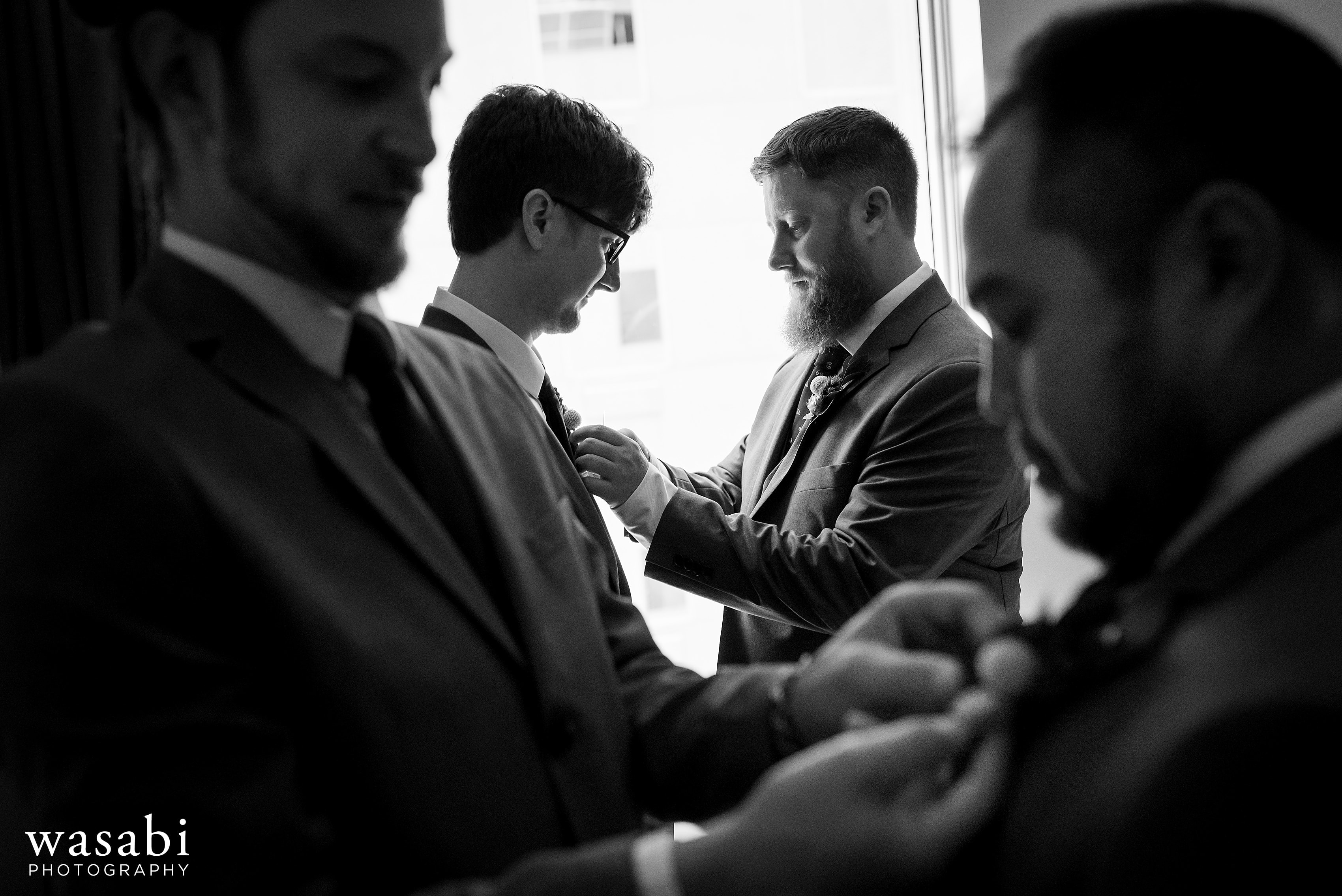 Groomsmen put their boutonnières on while getting ready for a wedding at La Quinta Inn & Suites in downtown Chicago