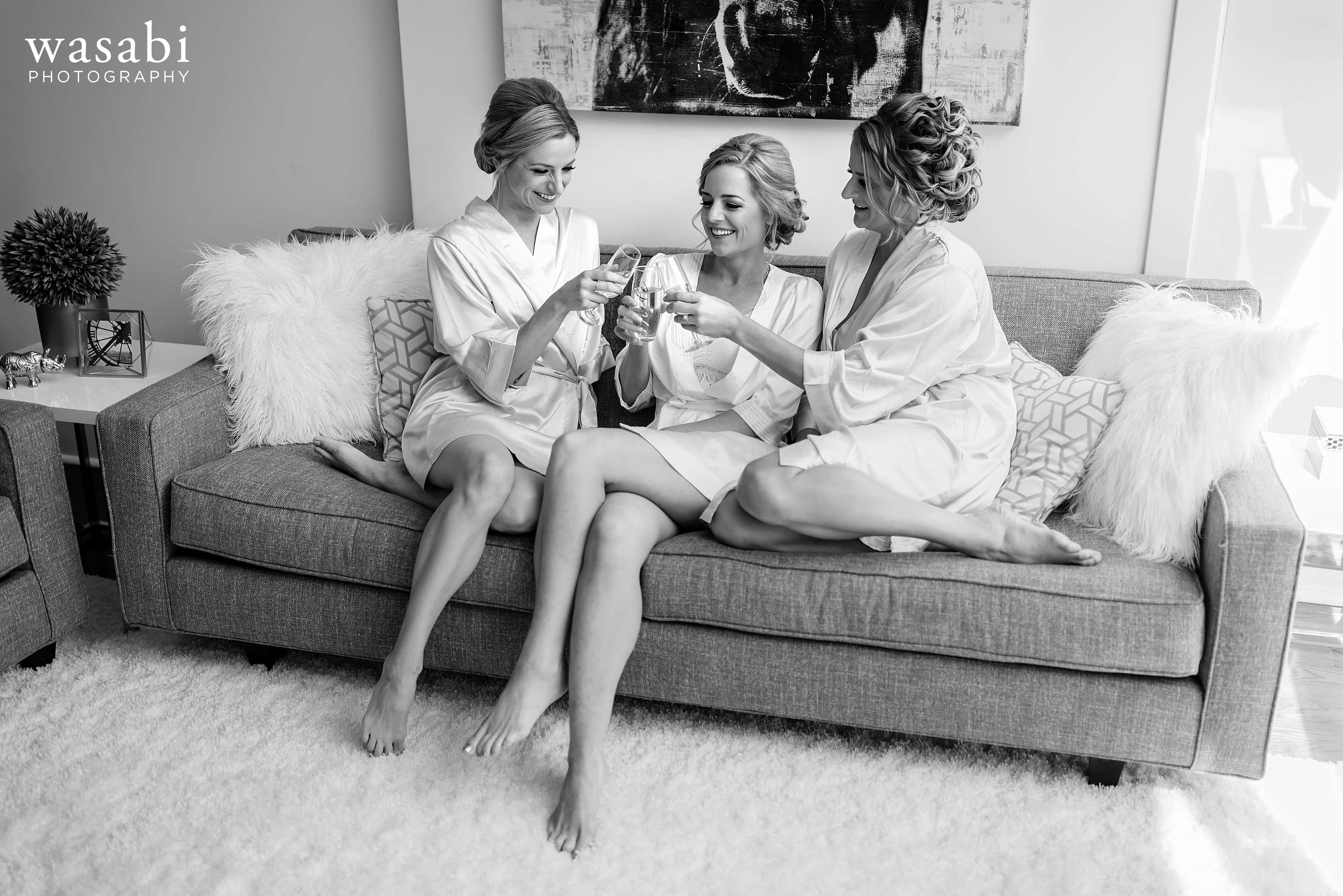 Bride and bridesmaids sisters toast on couch while getting ready for a wedding at home