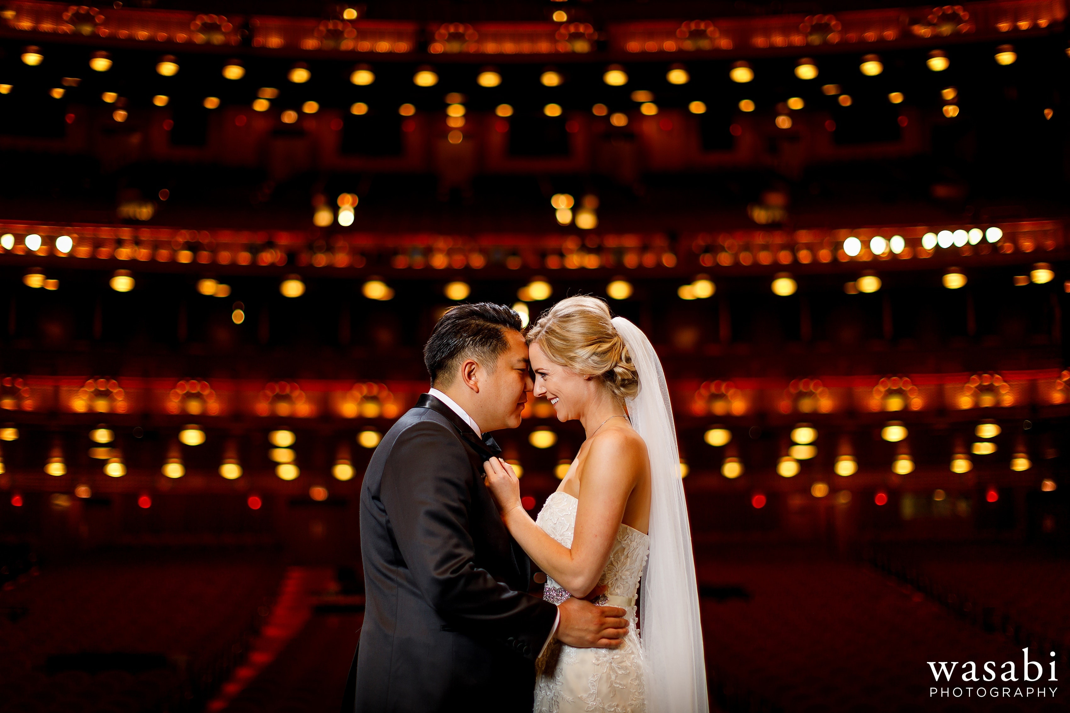 Bride and groom portrait on stage inside the Civic Opera Building in downtown Chicago with theatre in the background