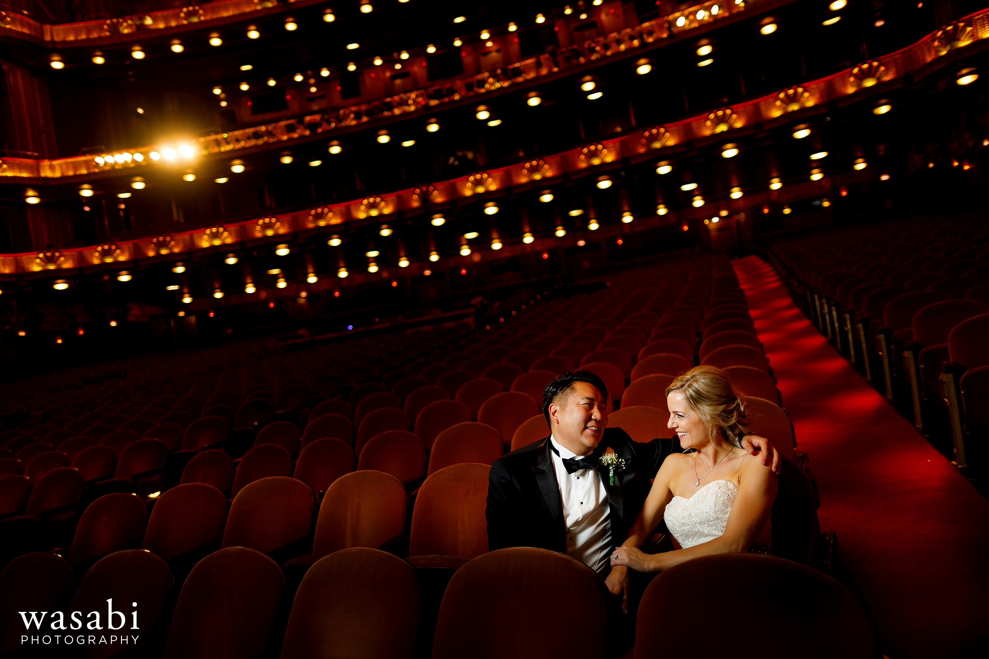 Bride and groom sit in chairs inside the theatre of the Civic Opera Building in downtown Chicago