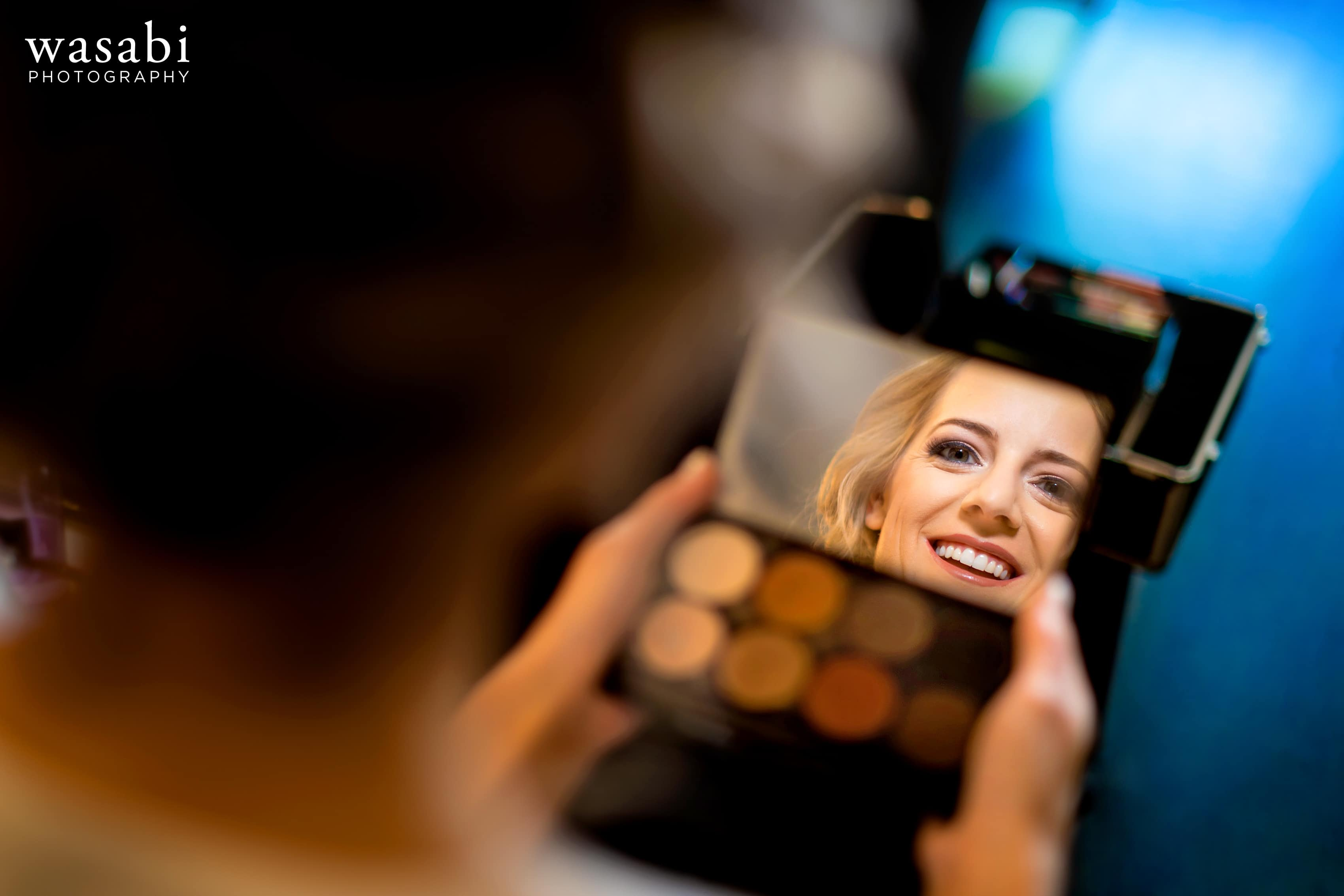 Bride looks into mirror while doing her makeup on wedding day