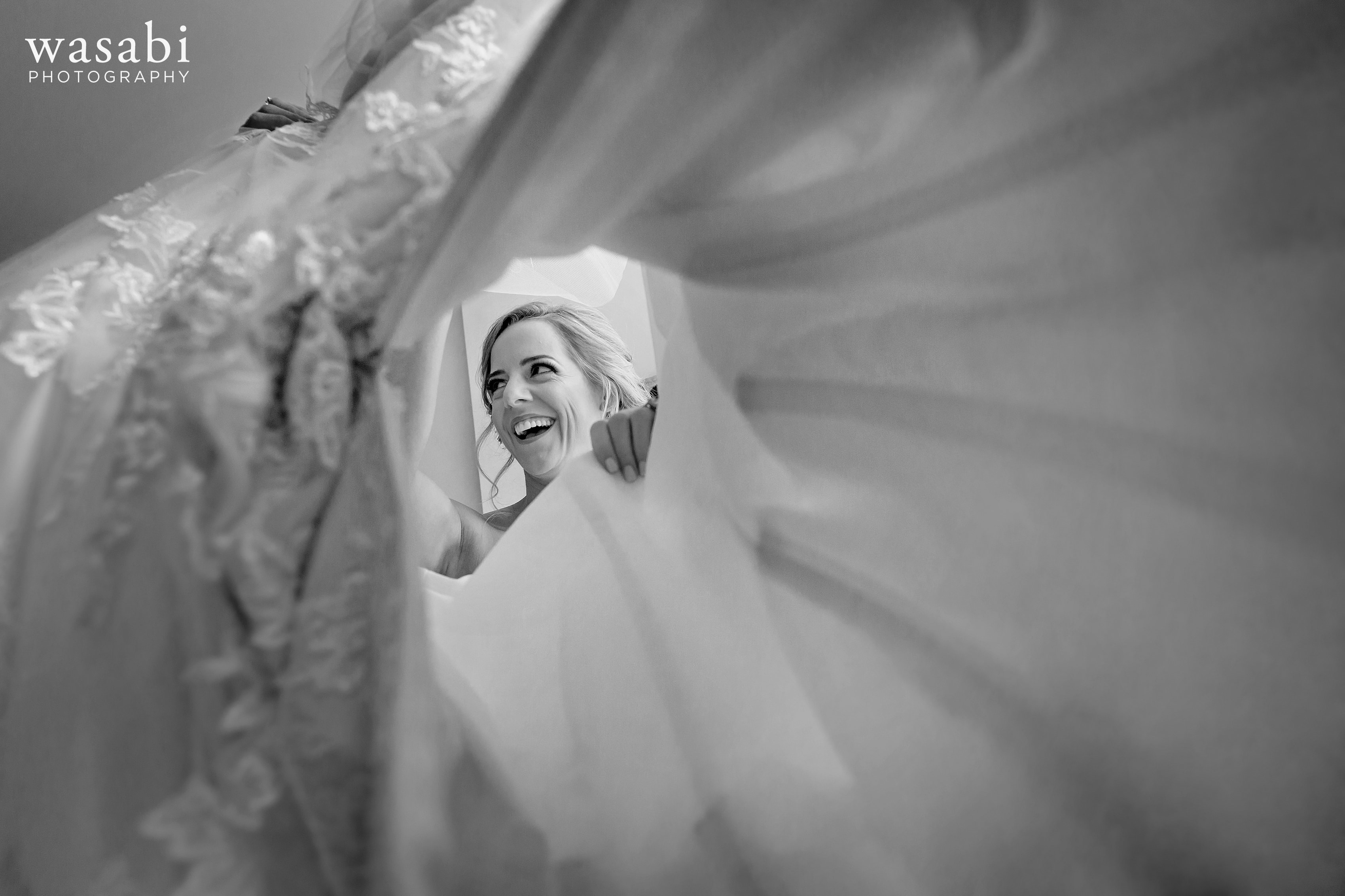 Bride puts on wedding dress creative photo looking through dress