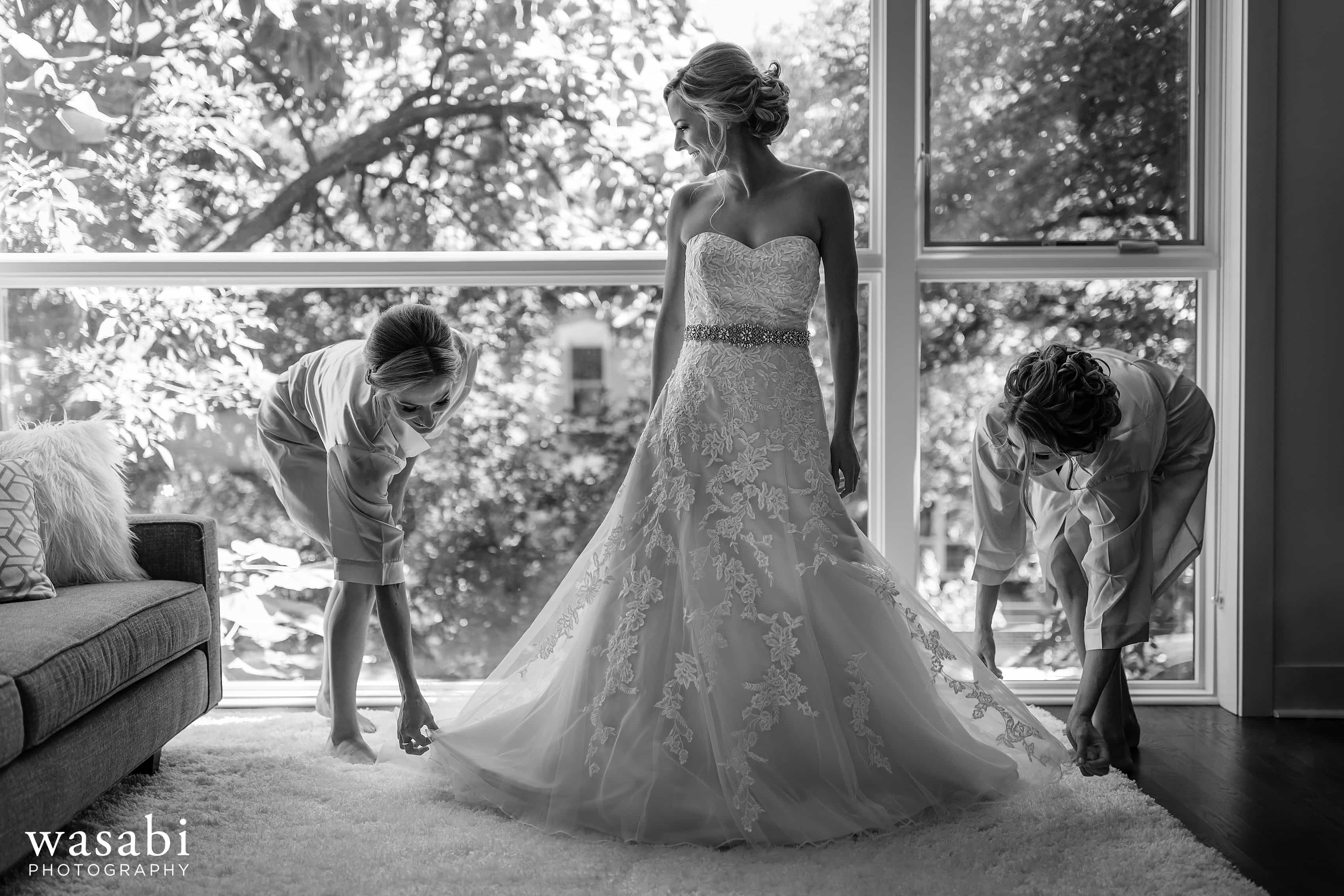 Bridesmaids help bride into dress at her home while getting ready for wedding