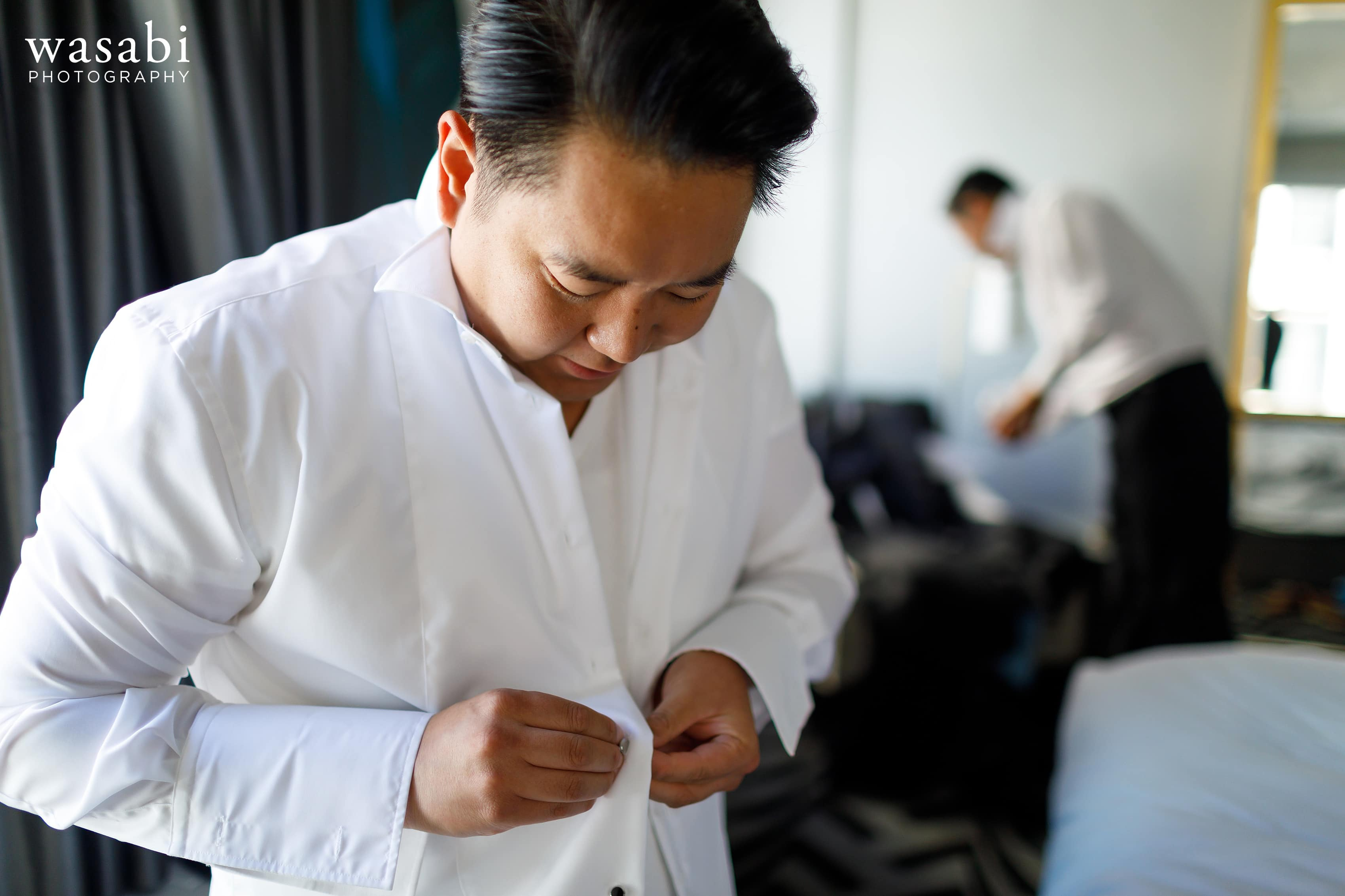 Groom buttons his shirt while getting ready for his wedding in hotel room
