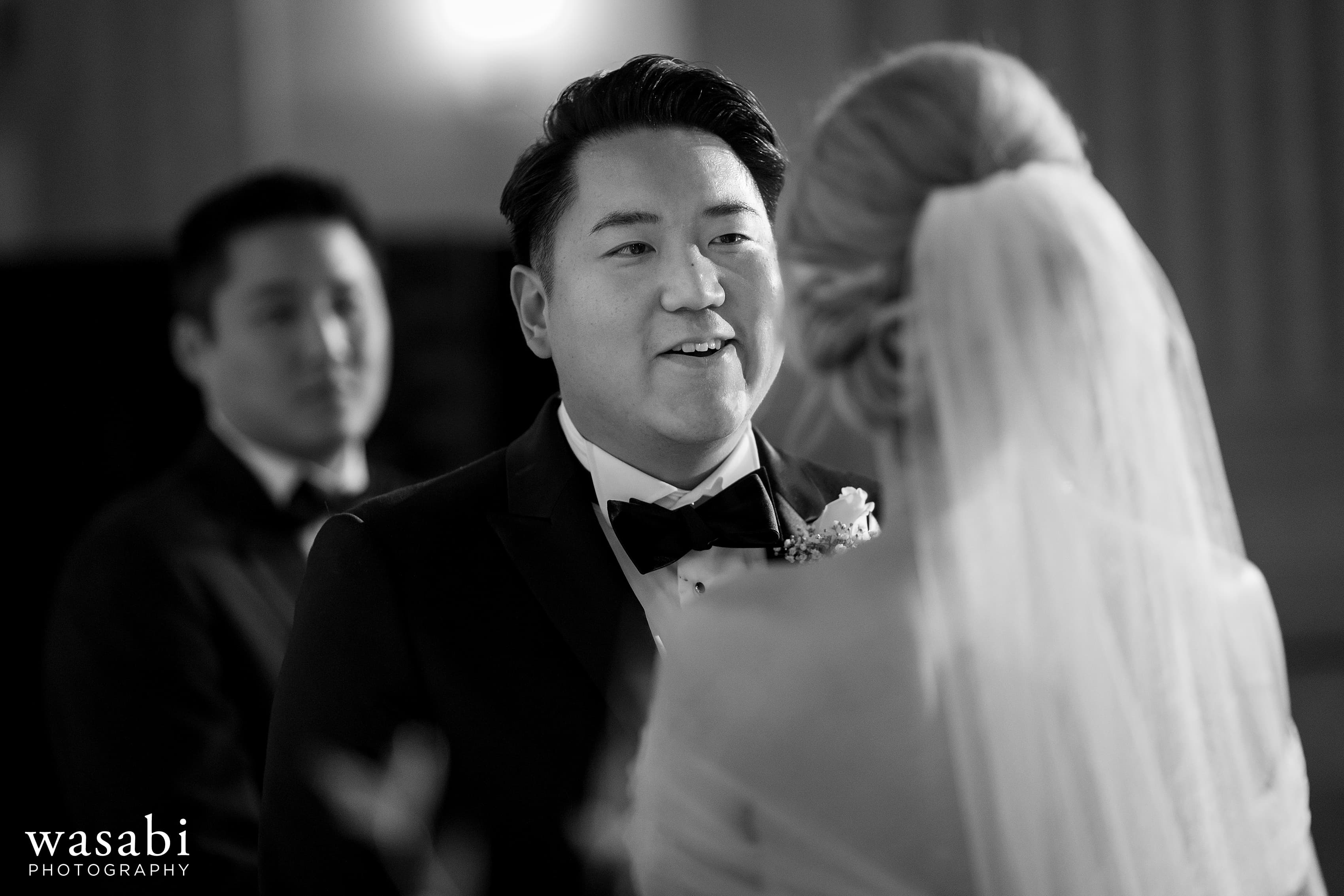 Groom smiles at bride during wedding at Civic Opera House in Chicago