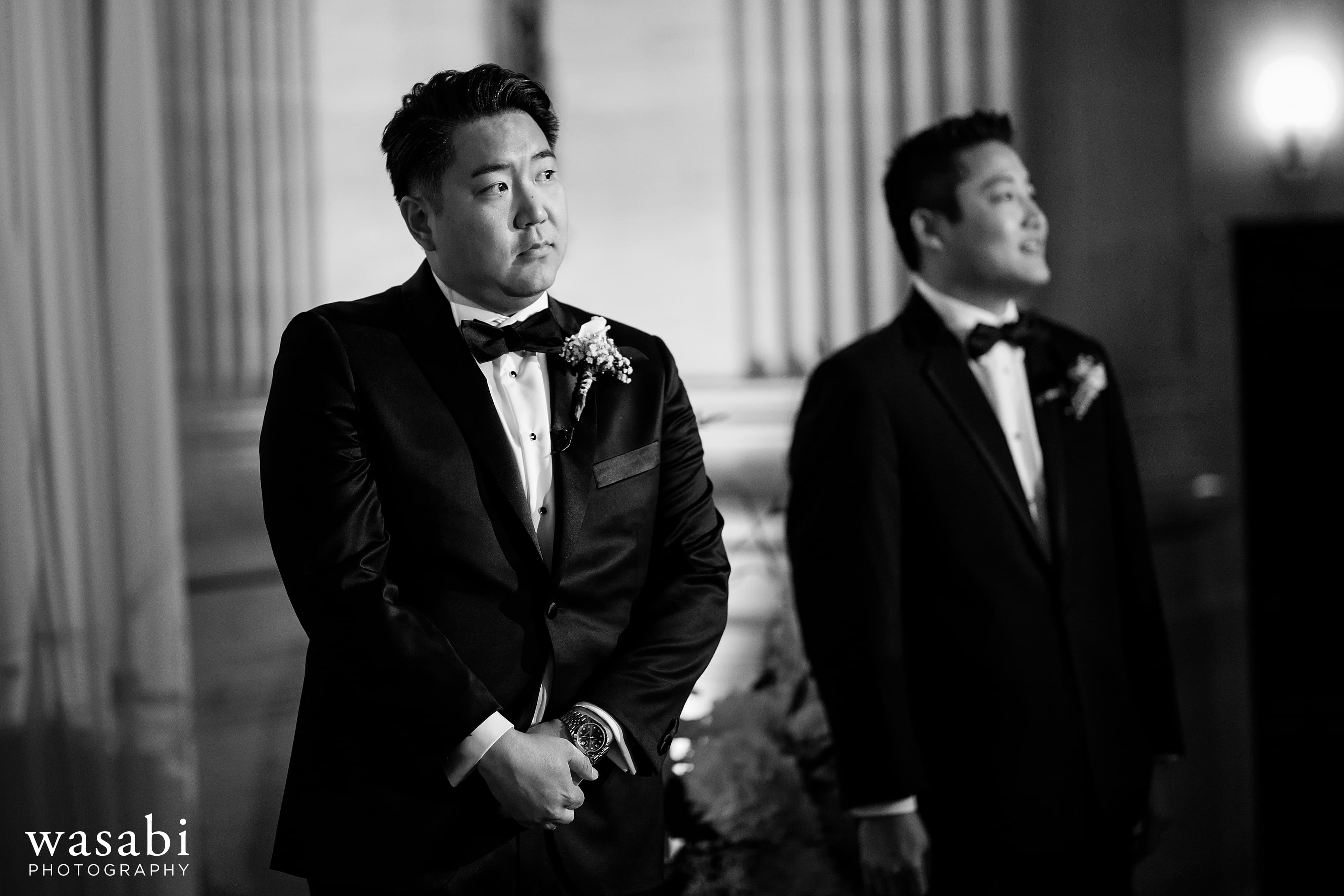 Groom watches while bride walks down the aisle during wedding at Civic Opera House in Chicago