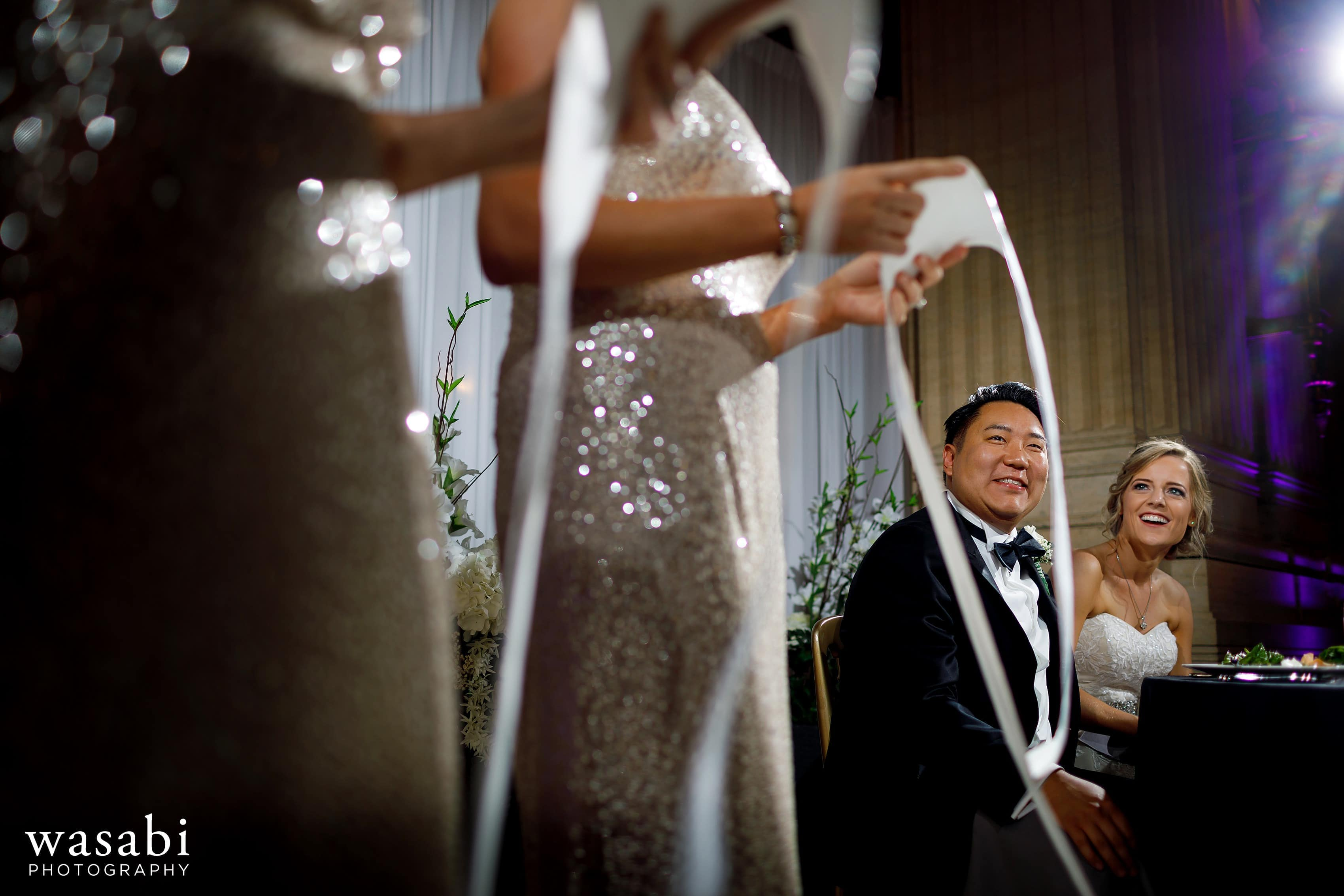 bride and groom laugh as bridesmaids read long scrolls as joke during toasts at Civic Opera House wedding reception in Chicago